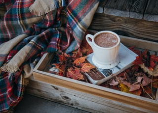 mug of chocolate drink on top of book beside fringed shawl