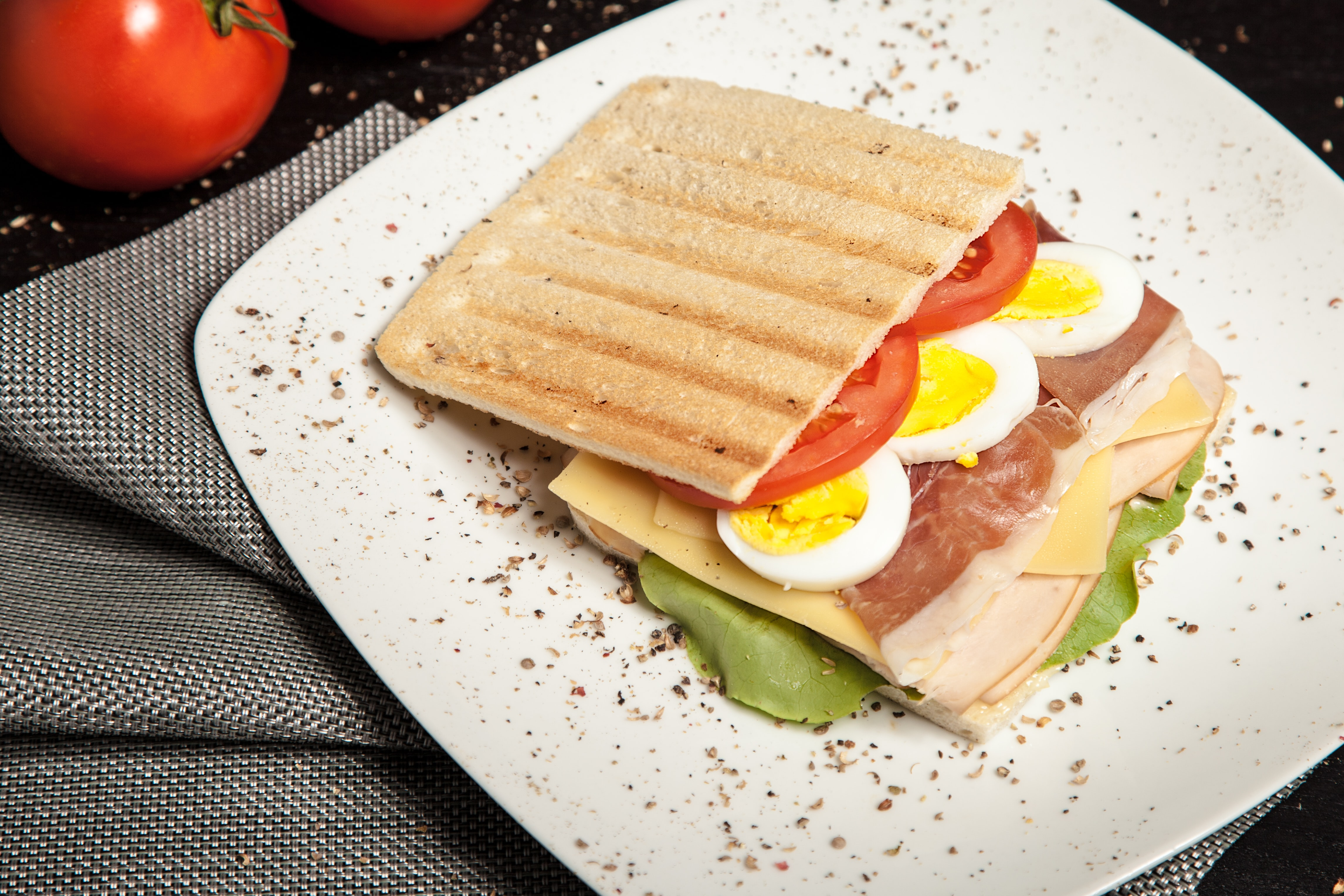 Toasted Russian sandwich with tomatoes, meat, eggs, and cheese