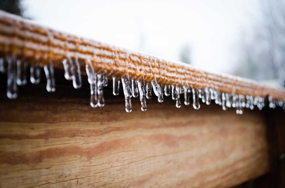 icicles forming at the edge of wooden panel