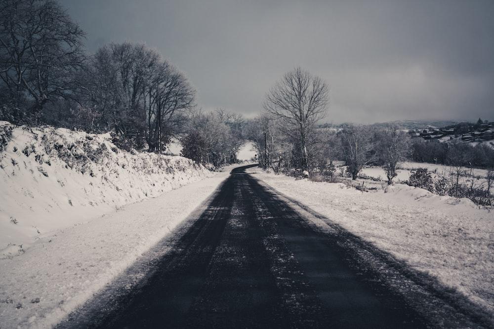 asphalt road across snowy field