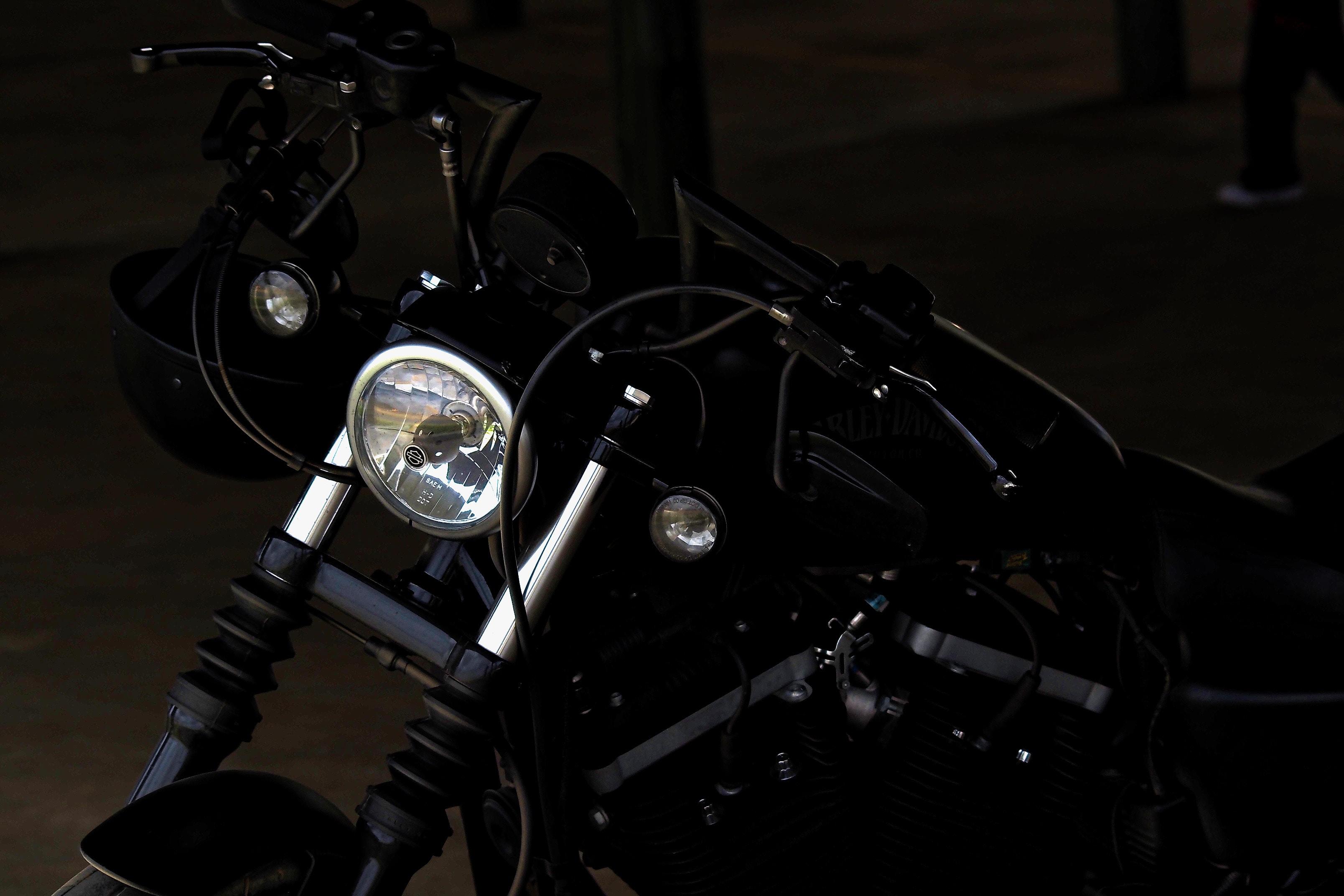 Black motorbike parked in a dark lot