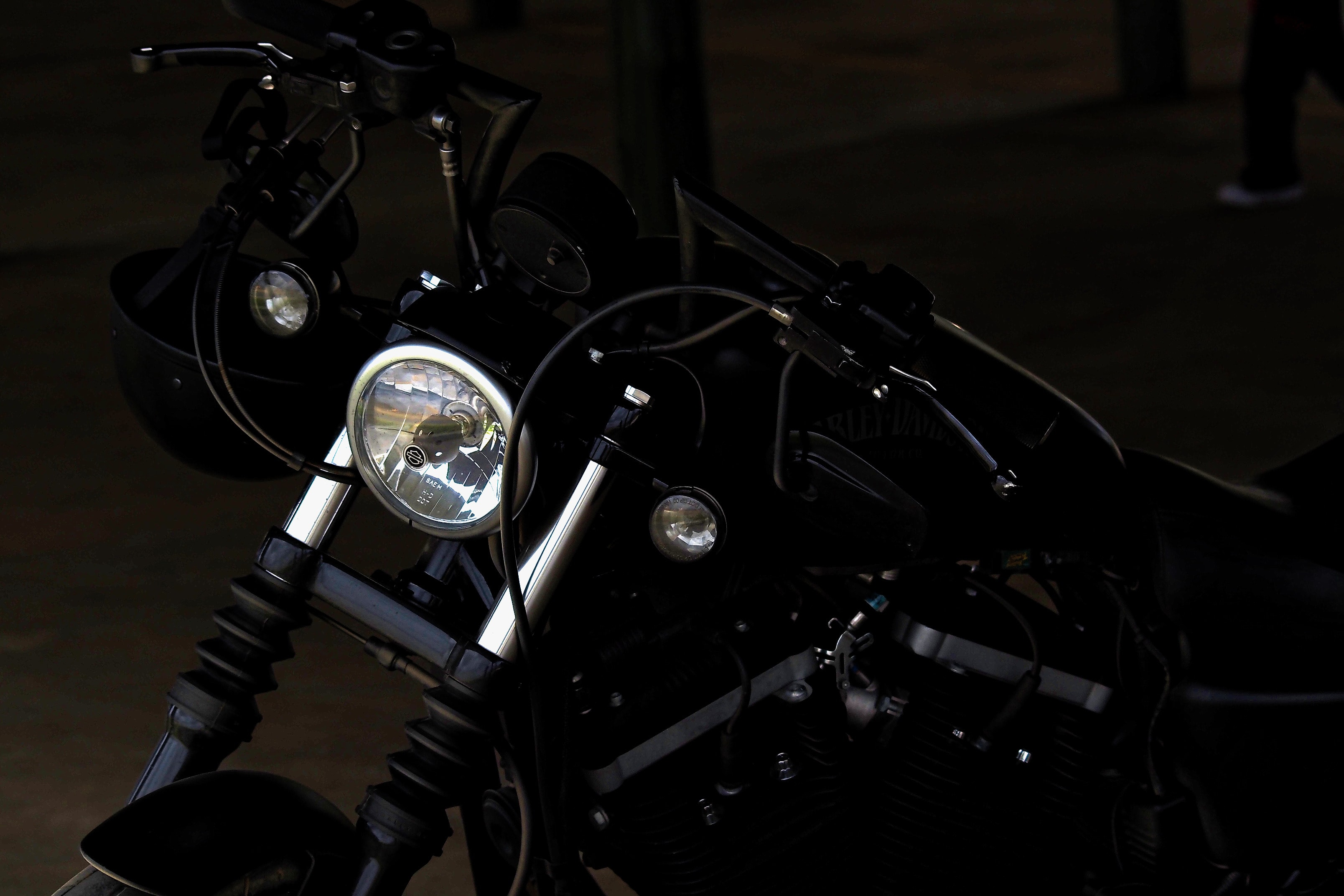 Black motorbike parked in a dark lot