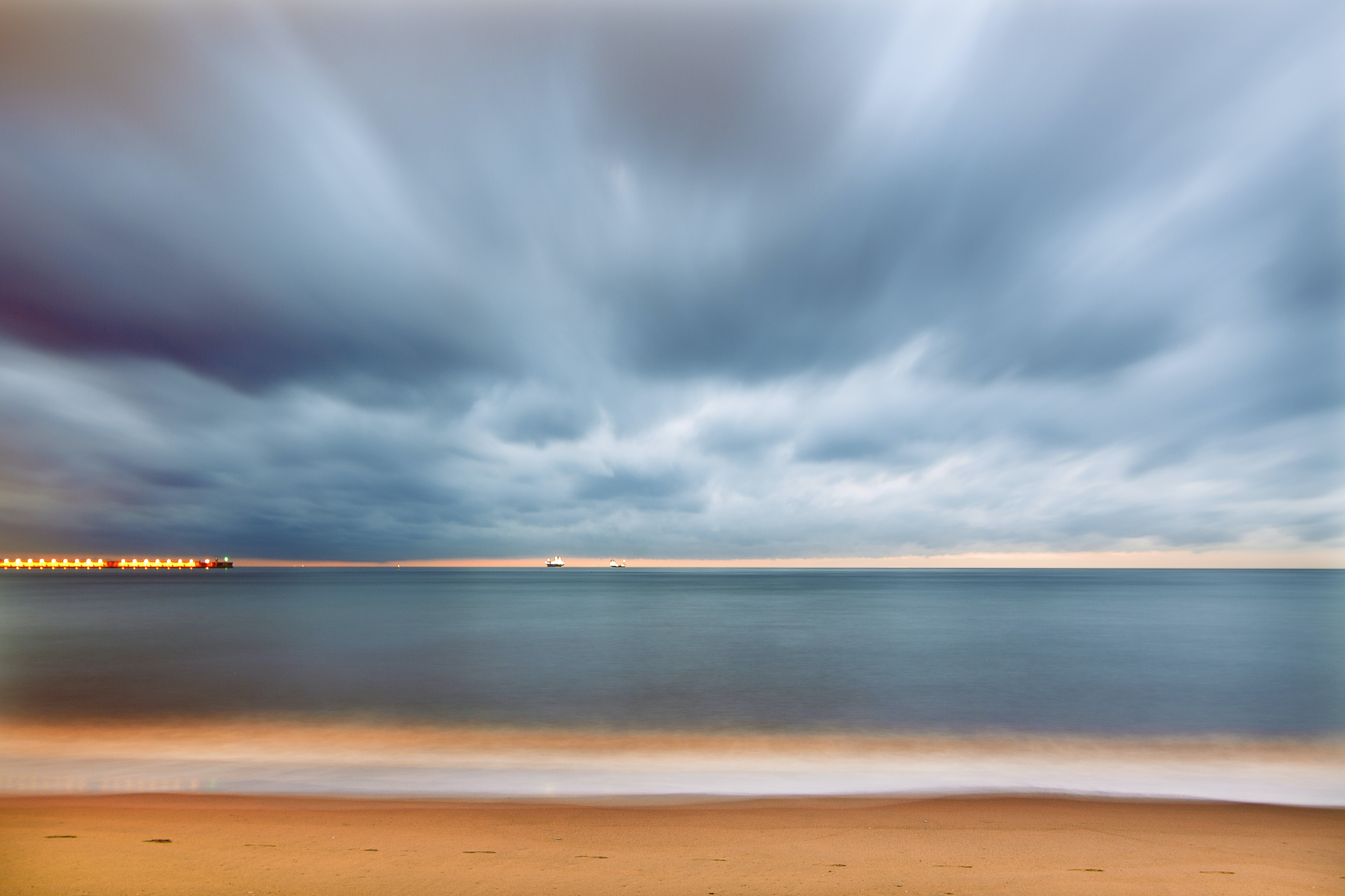 A scenic sunset with cloudy skies casting over Playa de la Misericordia in Malaga