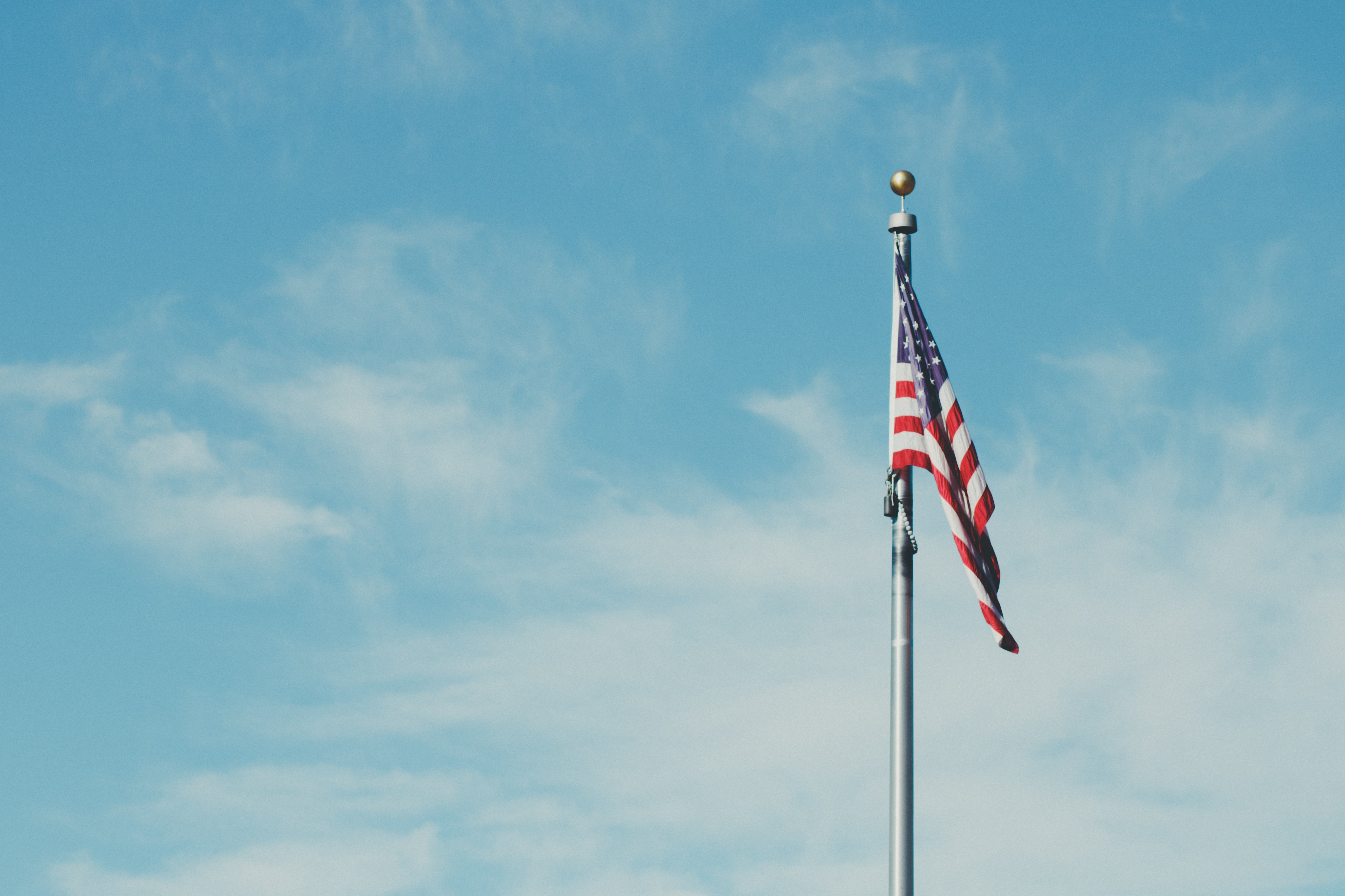 An American flag on a poll flying low against a blue sky
