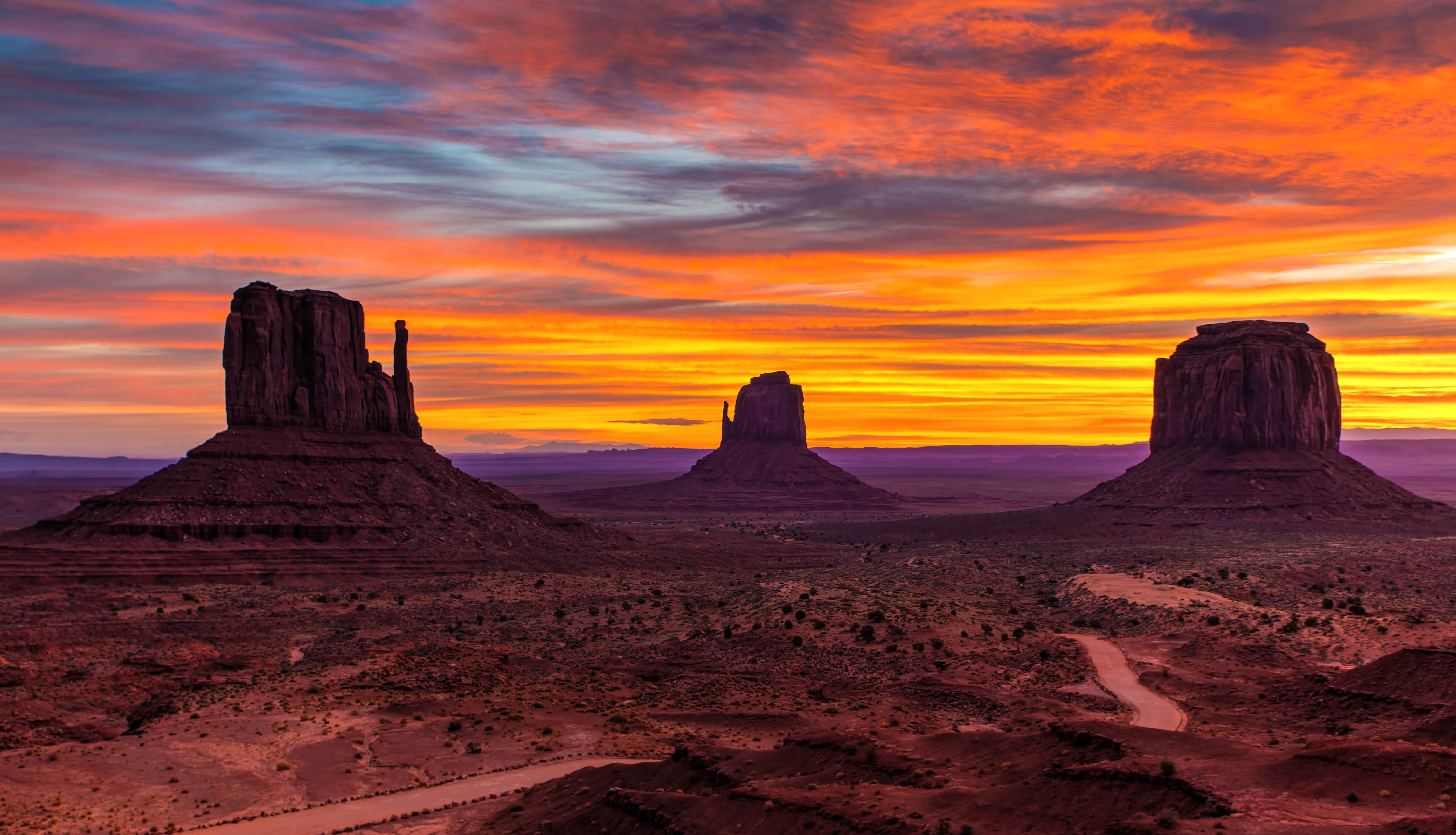 A bright orange and blue sunset covers the rock formations of Oljato-Monument Valley