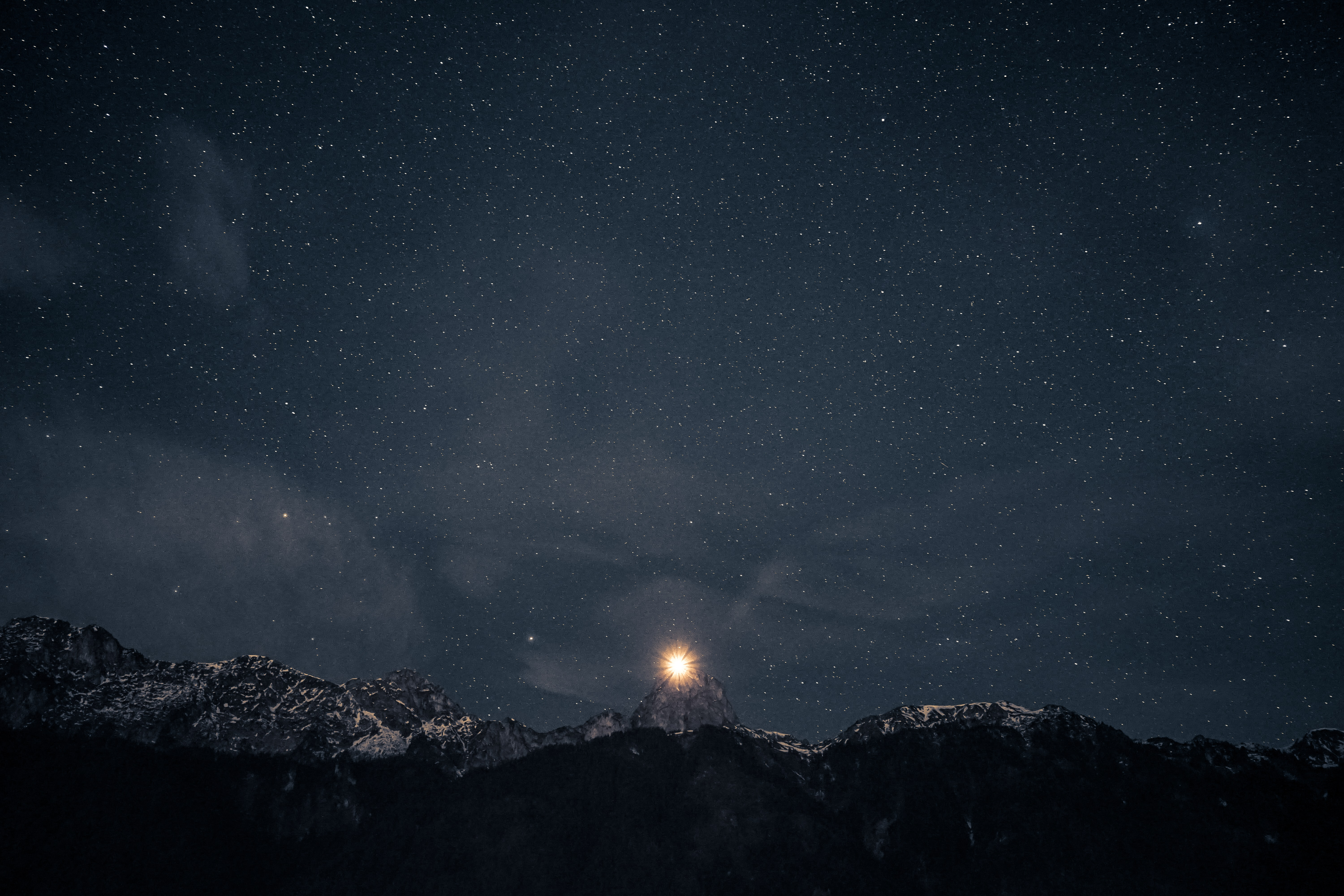 A bright star sits just above the top of a mountain during a starry night