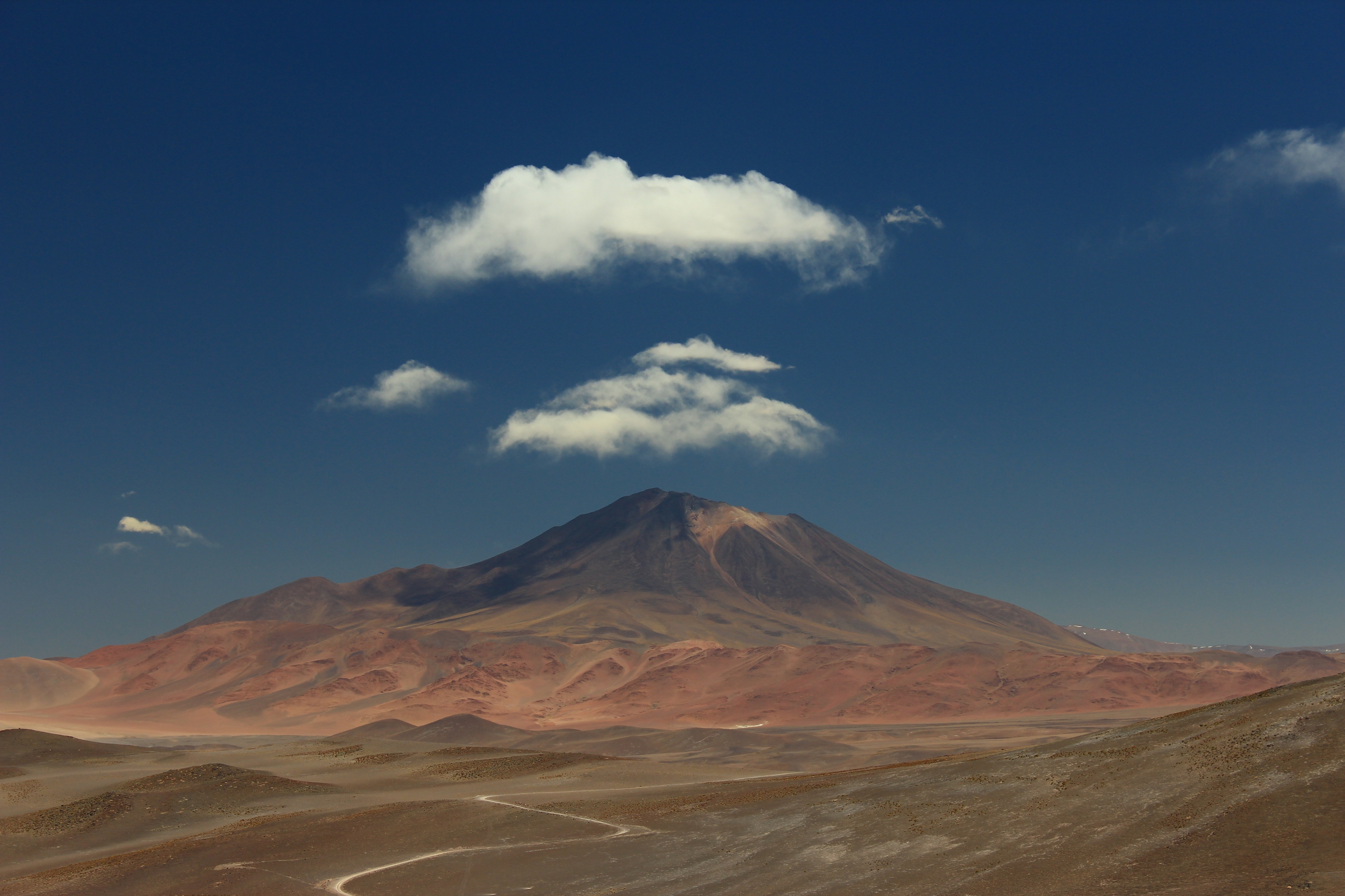 Fluffy clouds over a tall mountain with red rock slopes in Salar de Incahuasi