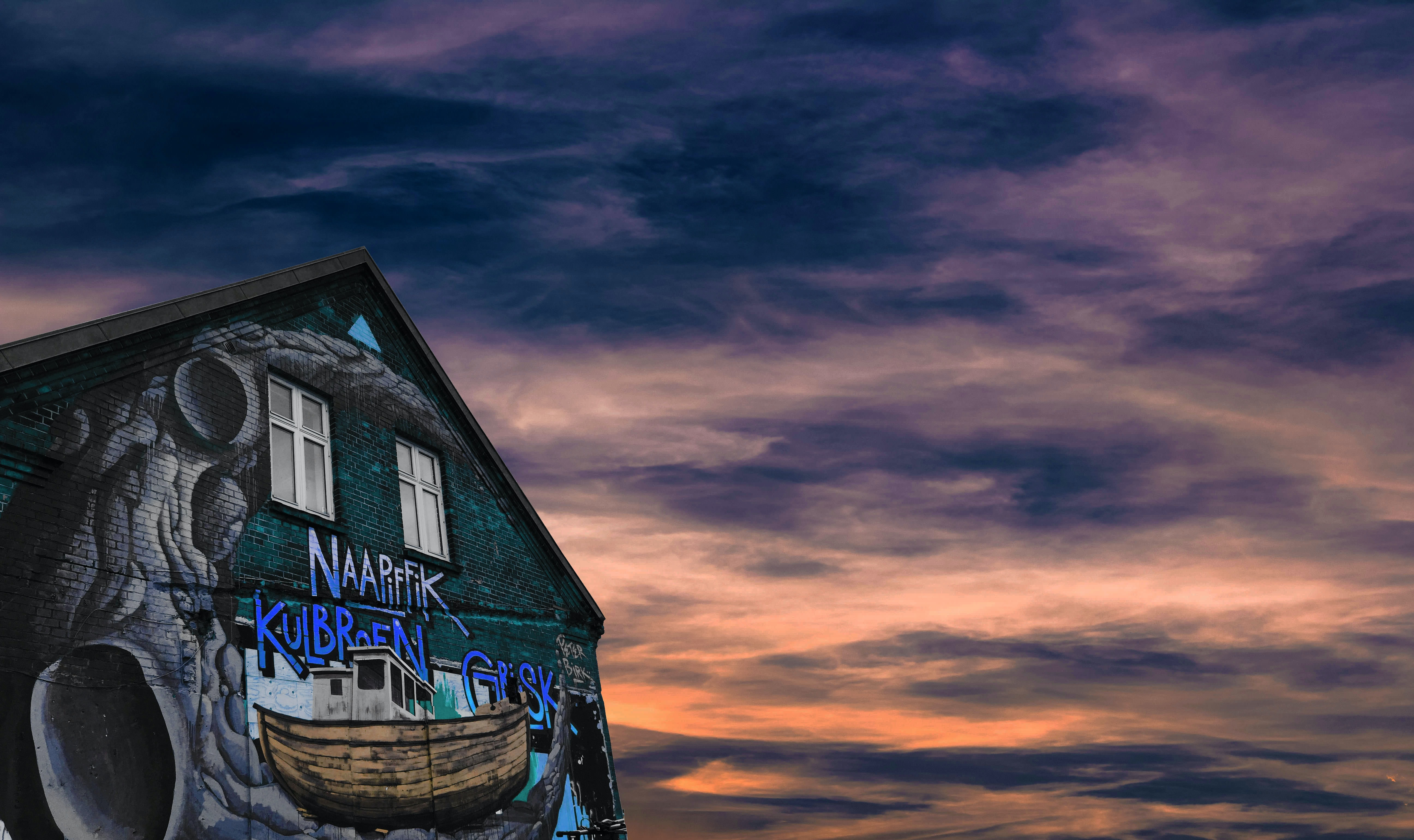 An abandoned looking graffiti covered building with a cloudy sunset in Aarhus, Denmark