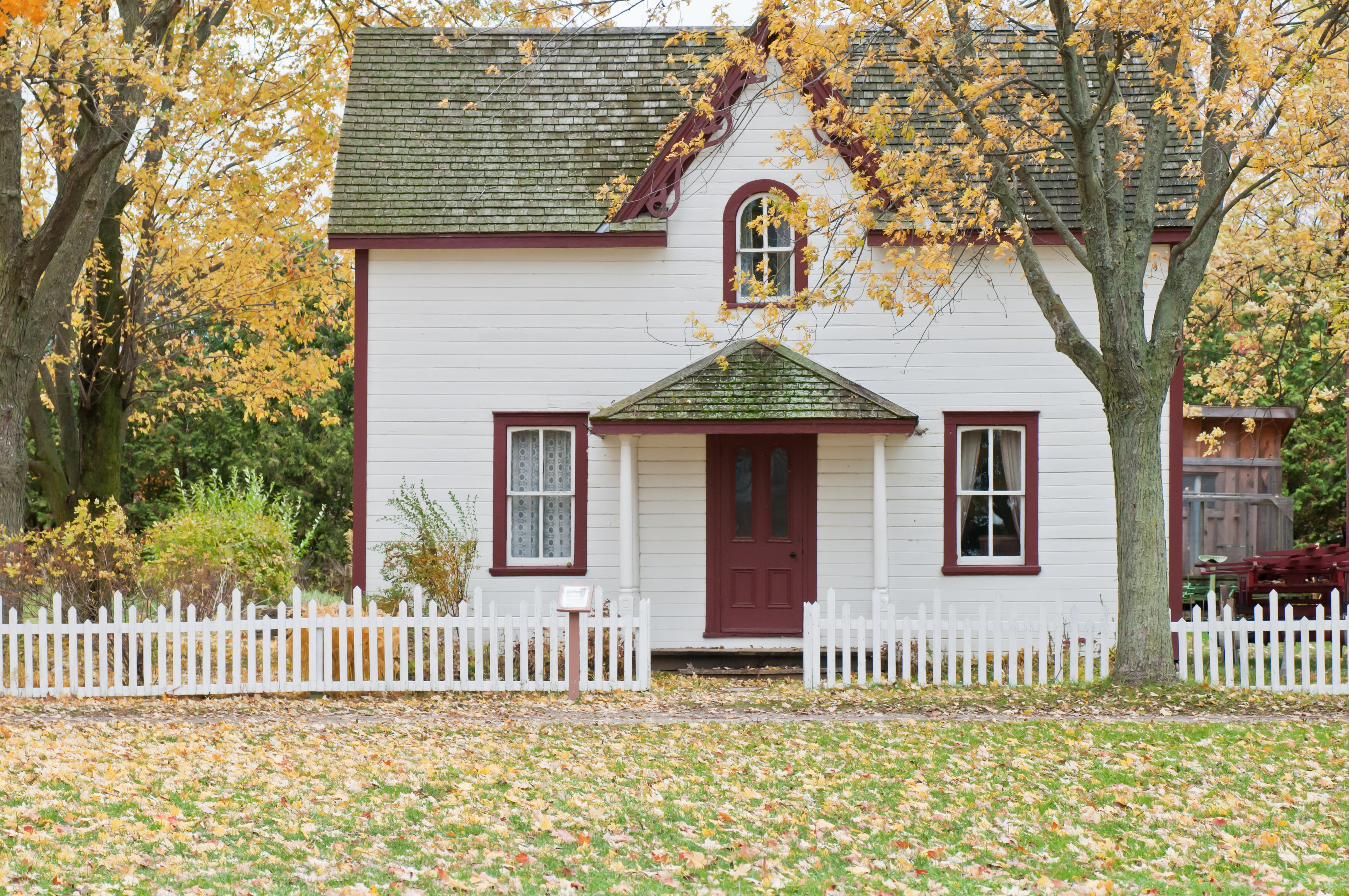 A small white house surrounded by trees in the autumn
