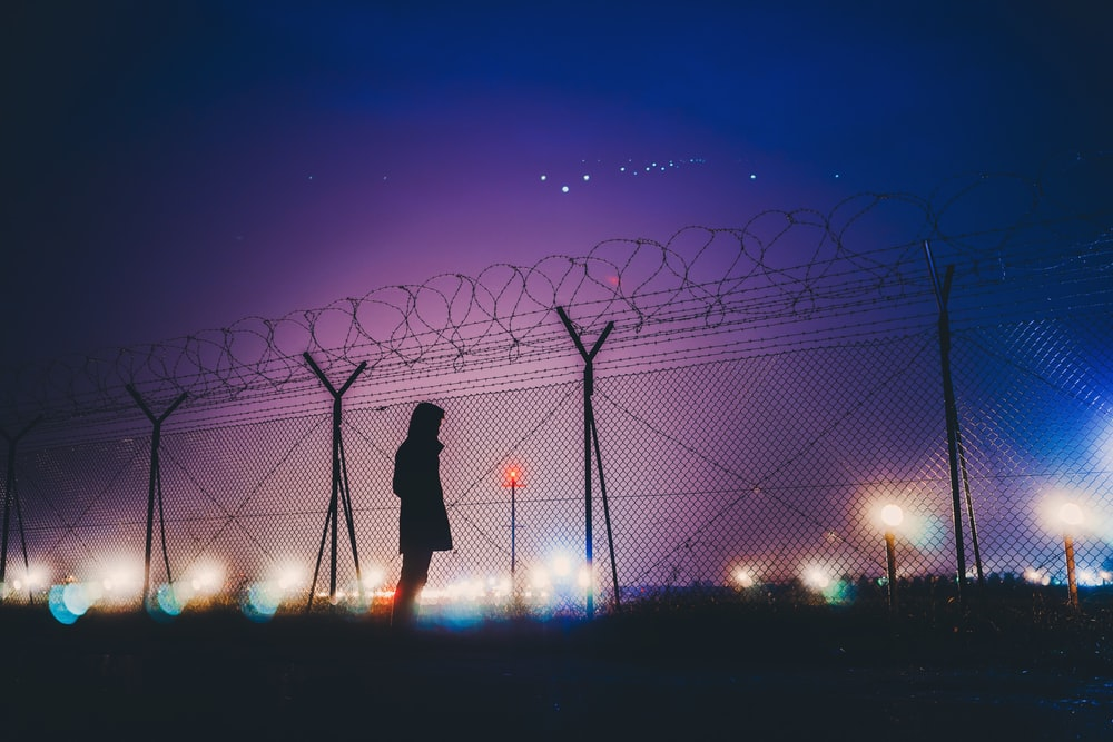 person's silhouette standing near chain link fence
