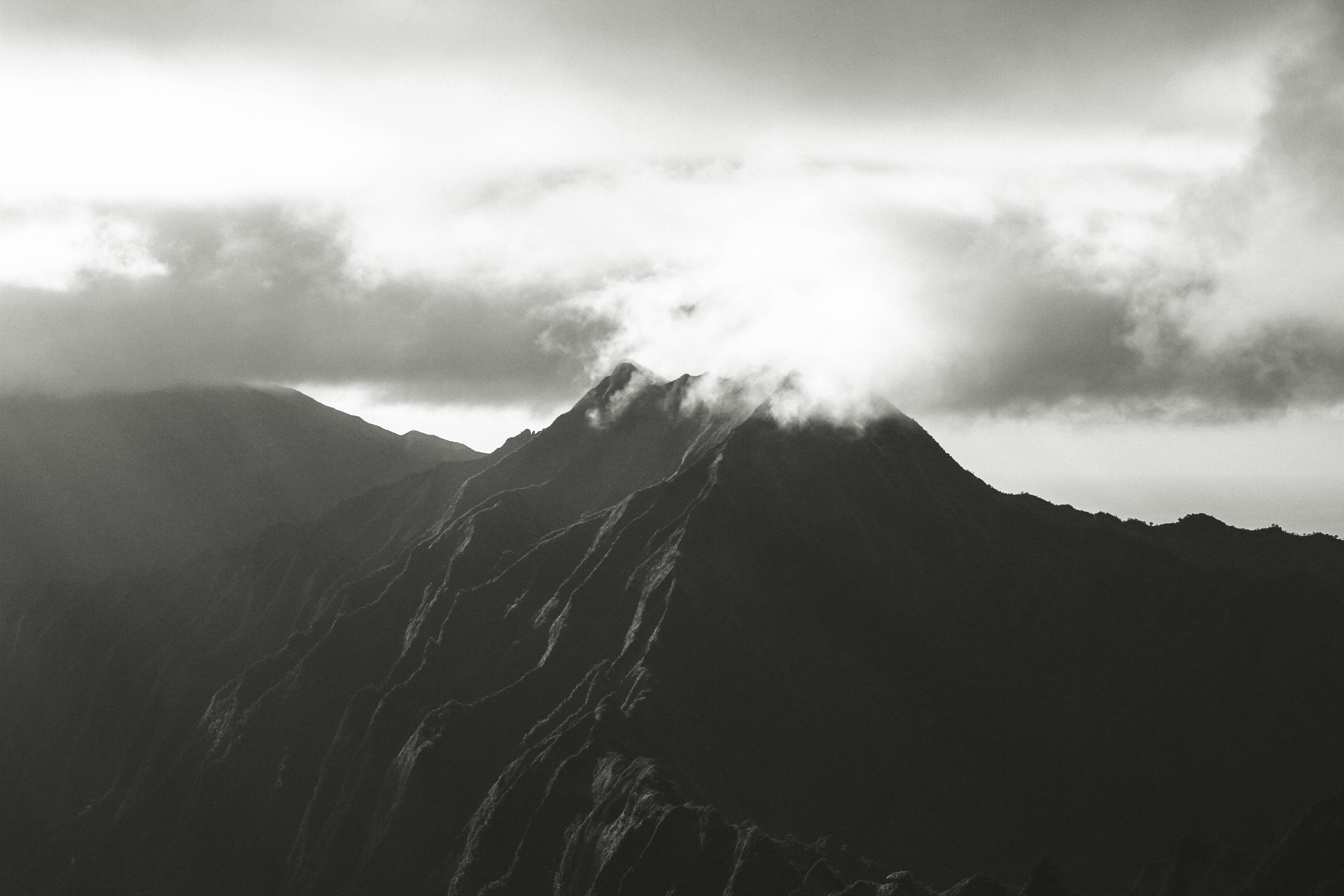 A black and white photo capturing the sun rising over a mountain in Hawaii.