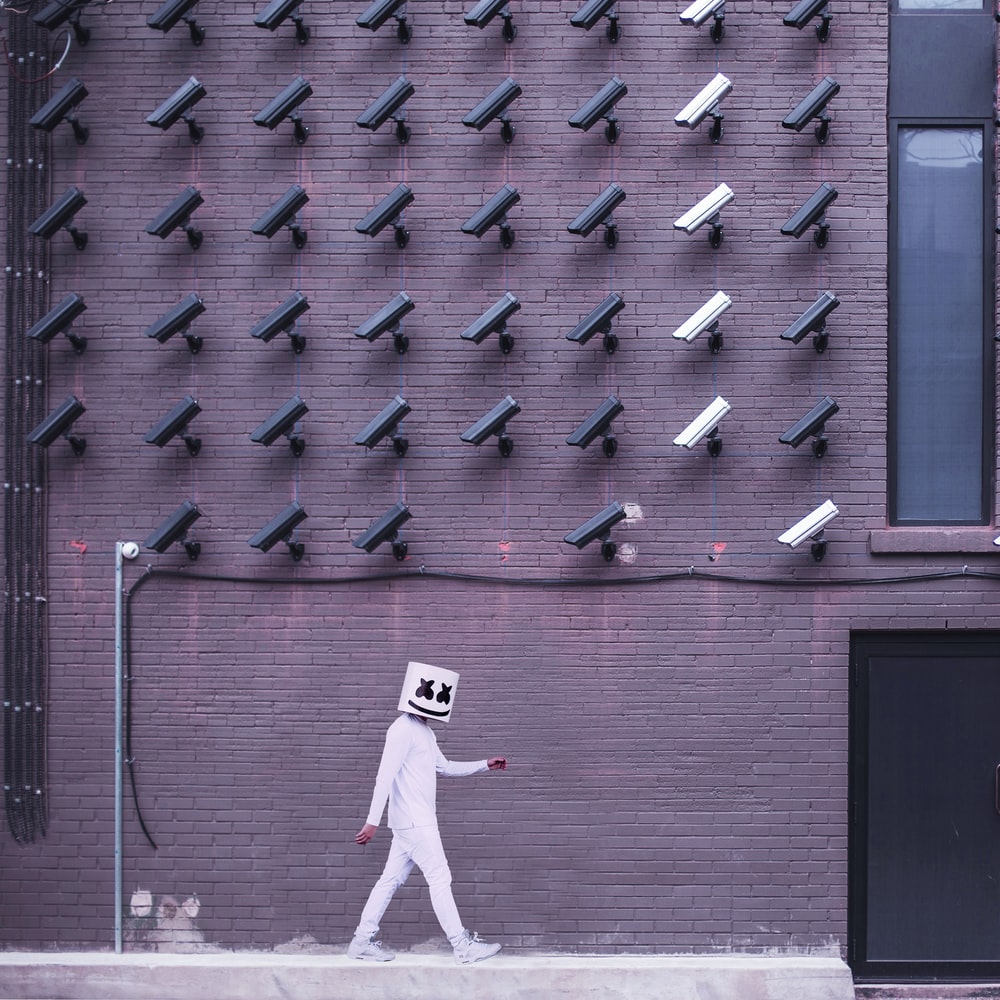 Marshmello walking down the side of the road with camera on the top of the building