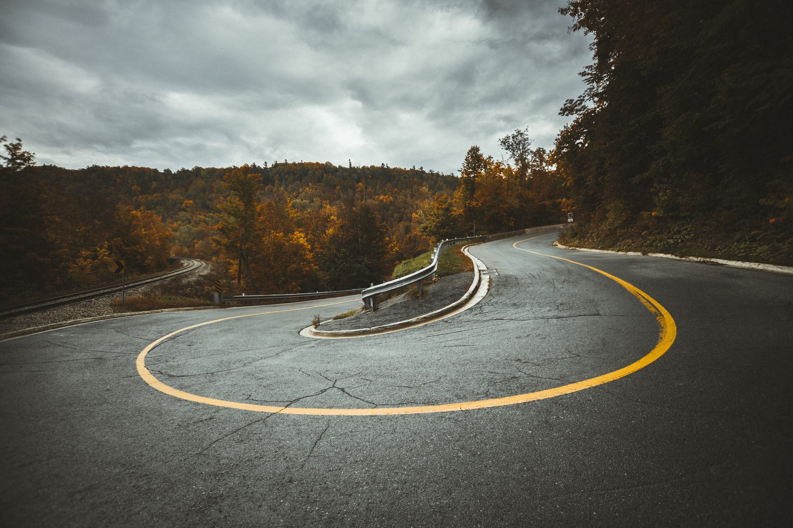 A sharp curve in an asphalt road surrounded by autumn-colored trees in Caledon