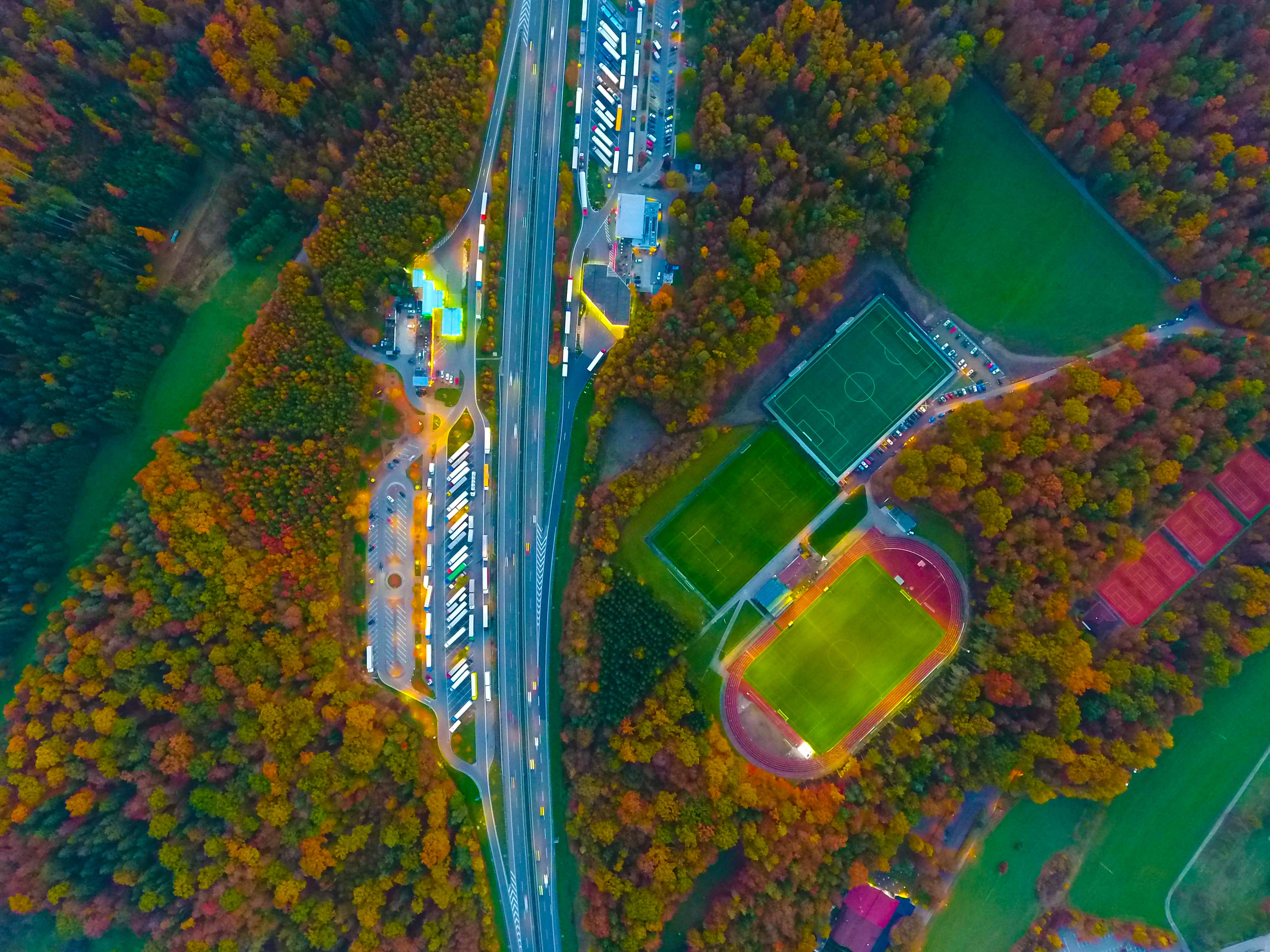 A colorful aerial shot of a highway running next to soccer pitches with light reflecting off buildings