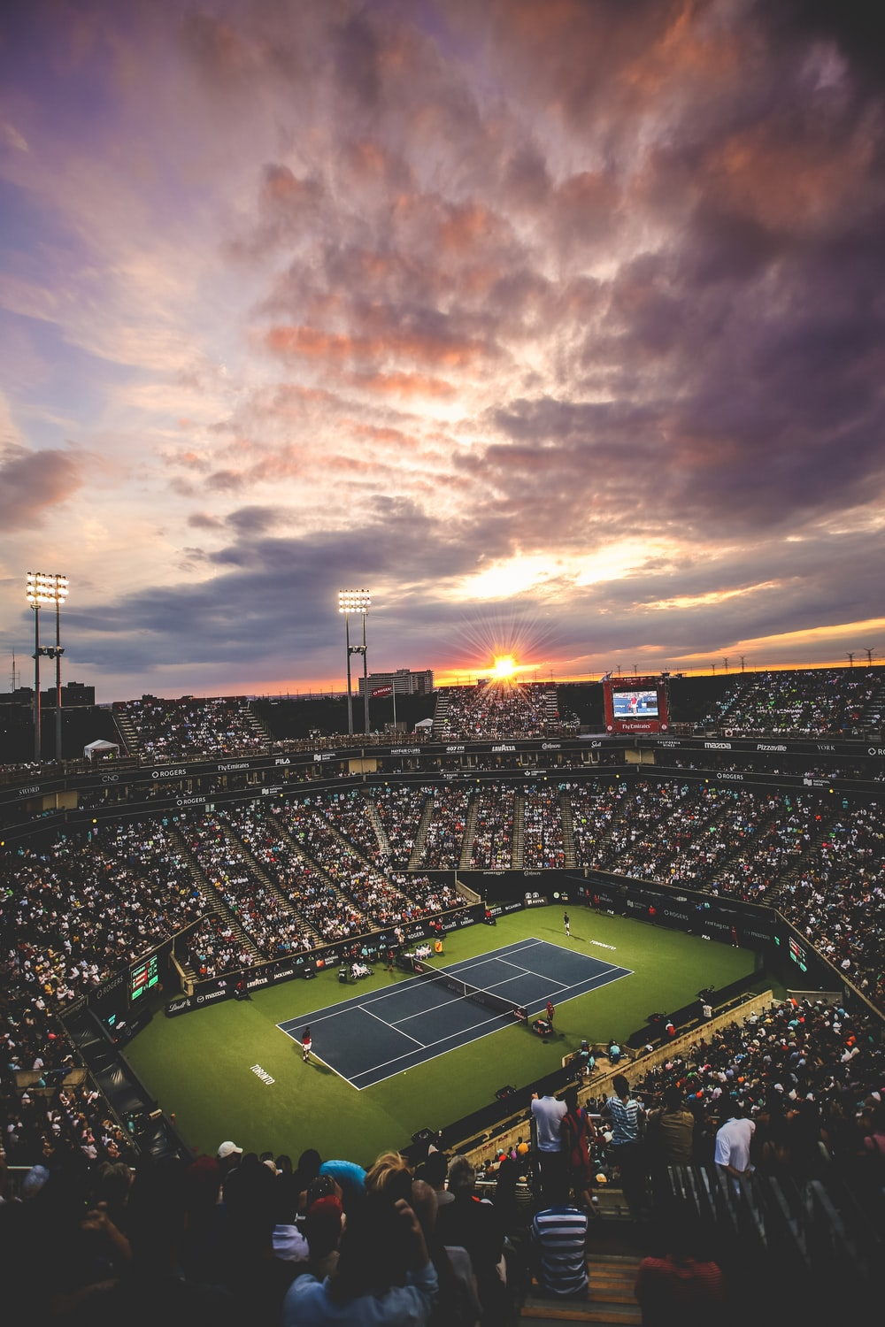 people at the tennis court stadium during sunset