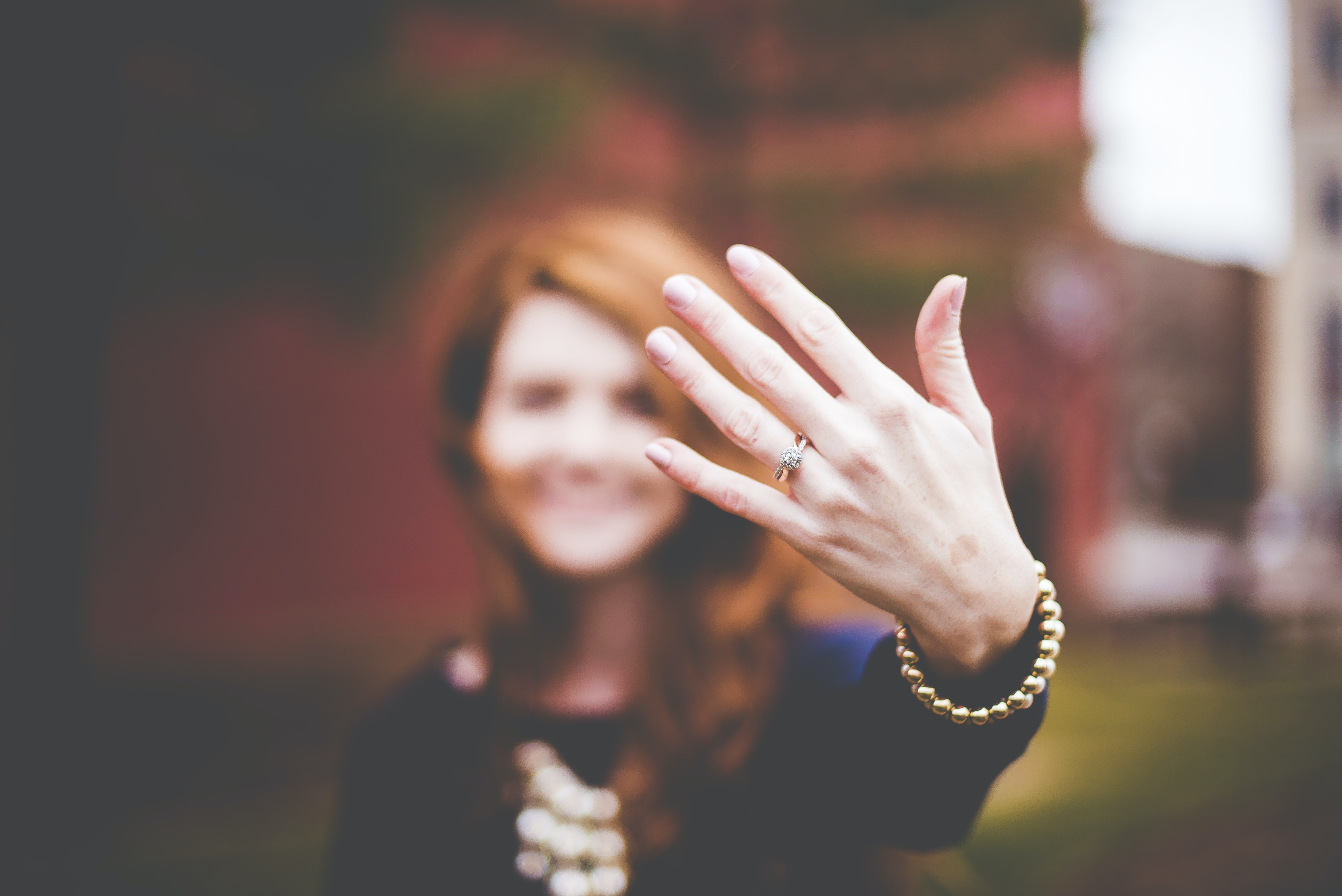 A blurry woman in the background holds up the engagement ring on her hand