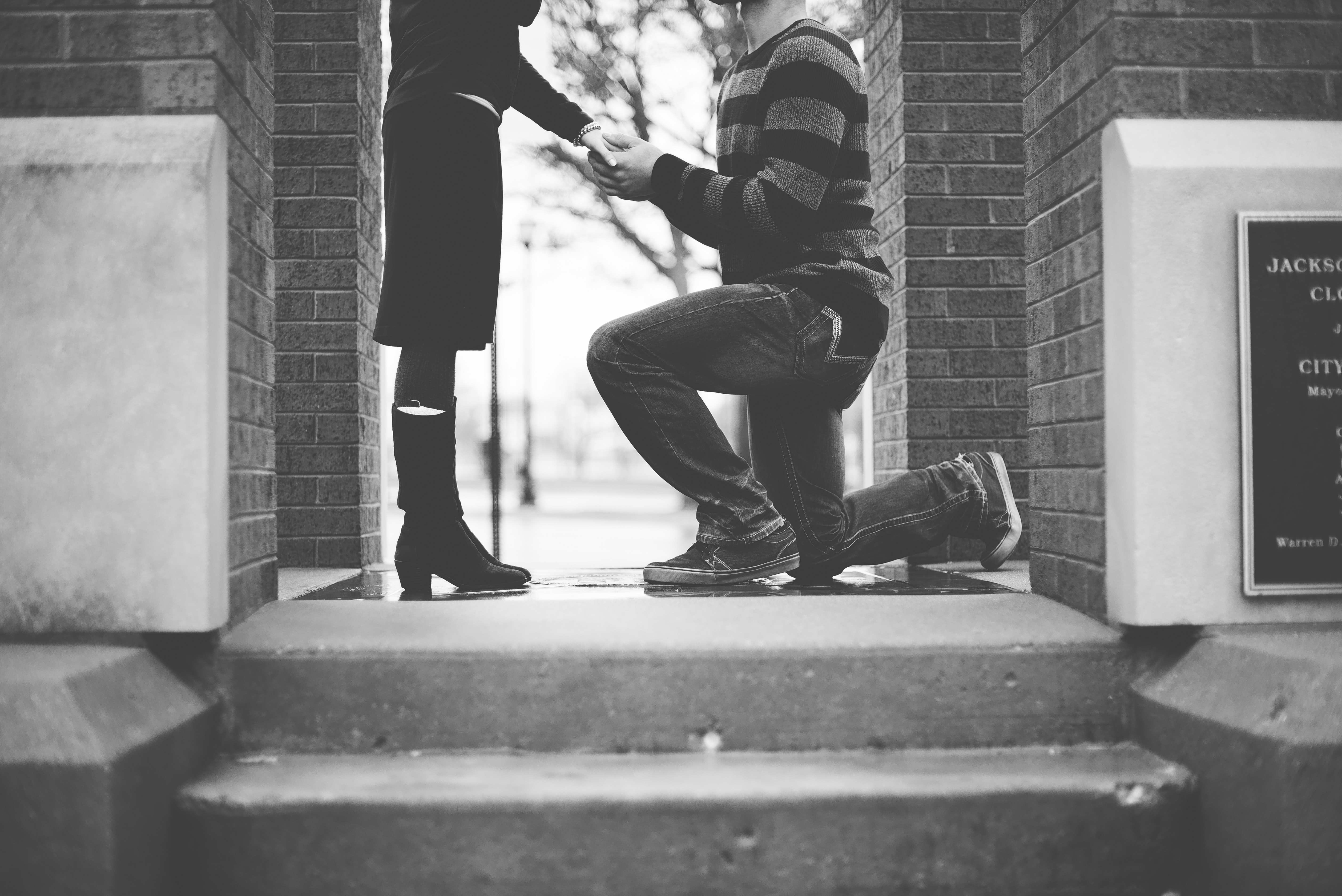 Black and white photo of man bent on one knew, proposing to his girlfriend