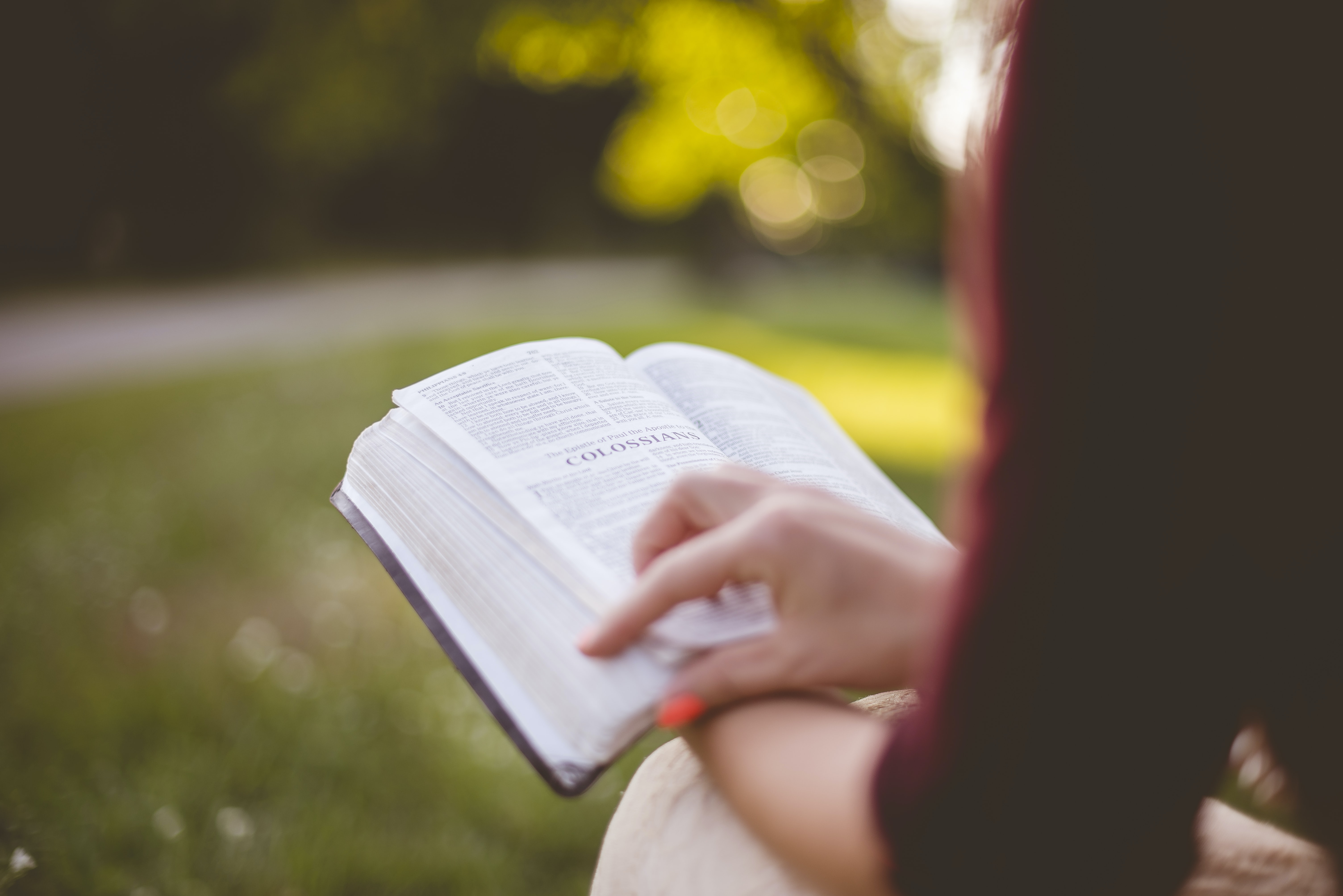 selective focus photography of person reading book