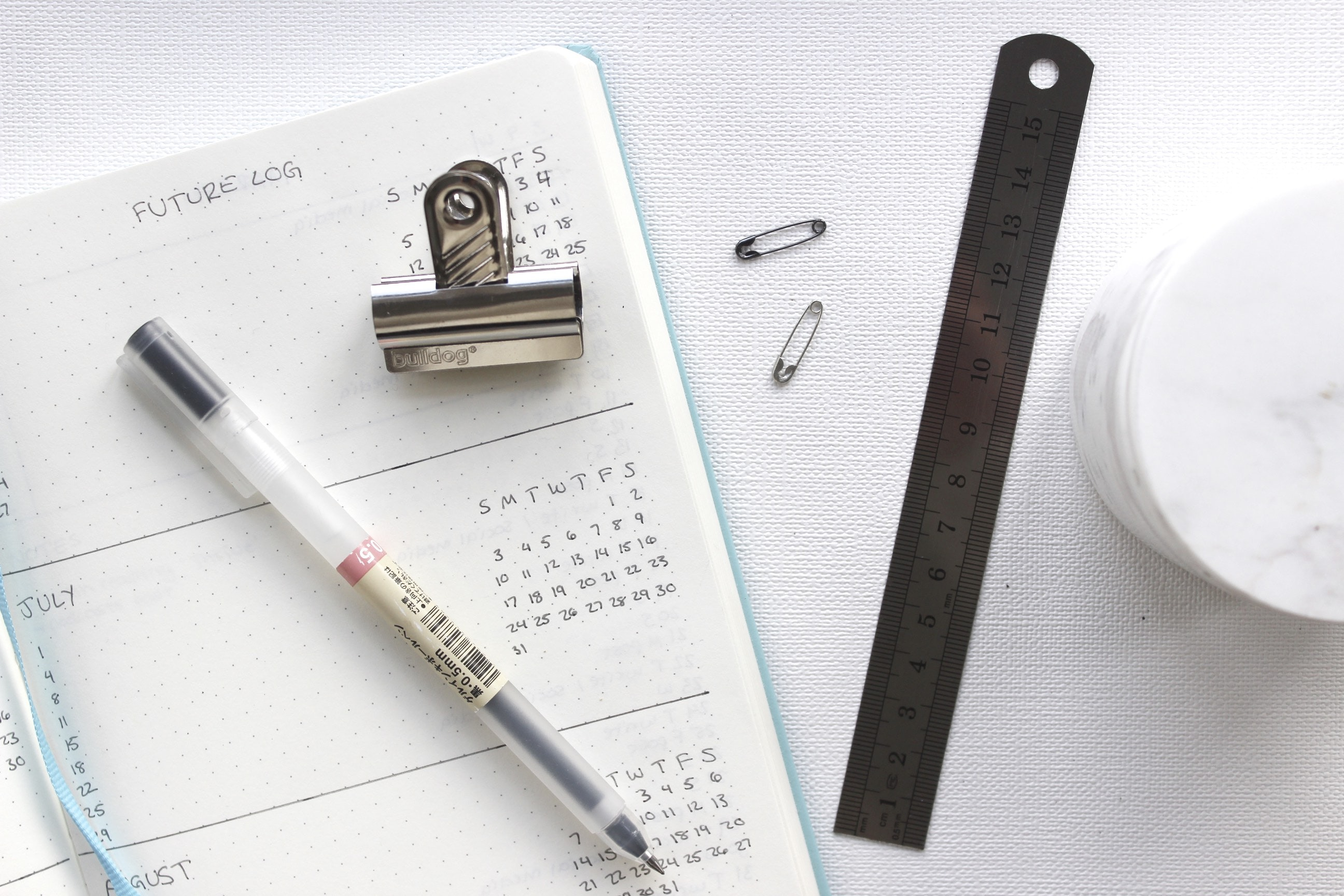 An agenda with a pen, clip, ruler and other items.