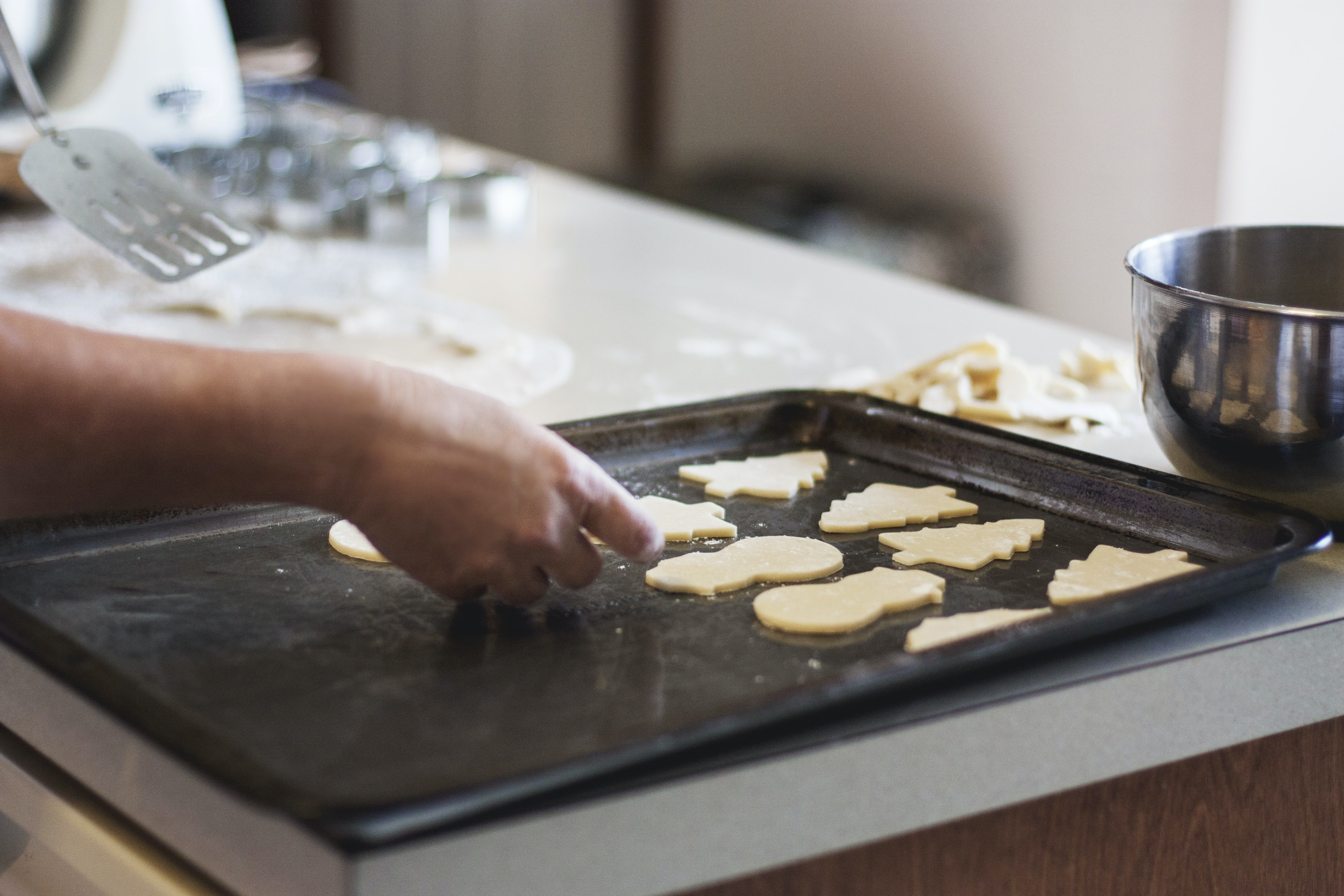 person lining assorted-shaped cookies on baking sheet inside kitchen