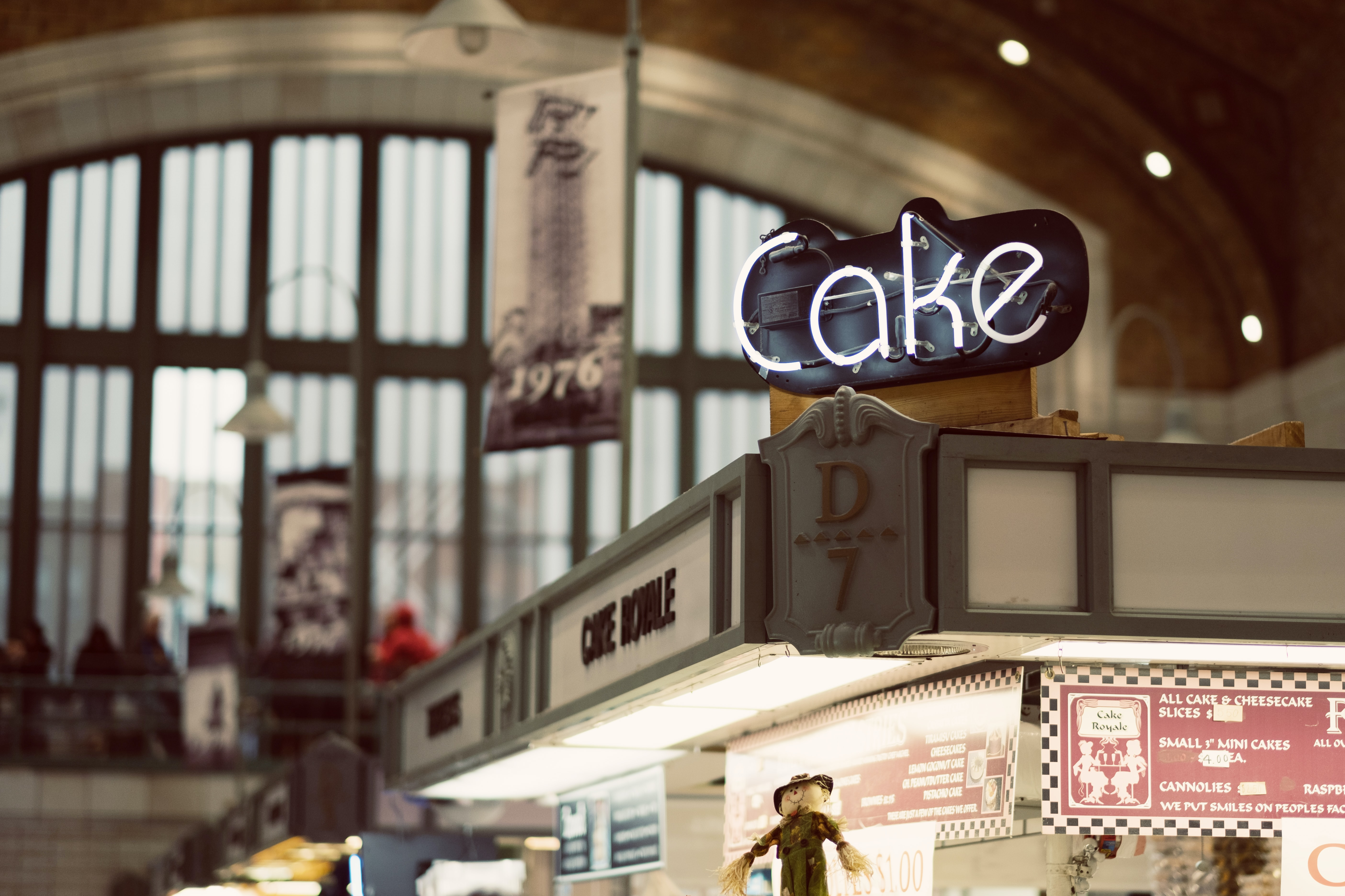 """A """"cake"""" neon over a store in a covered market"""