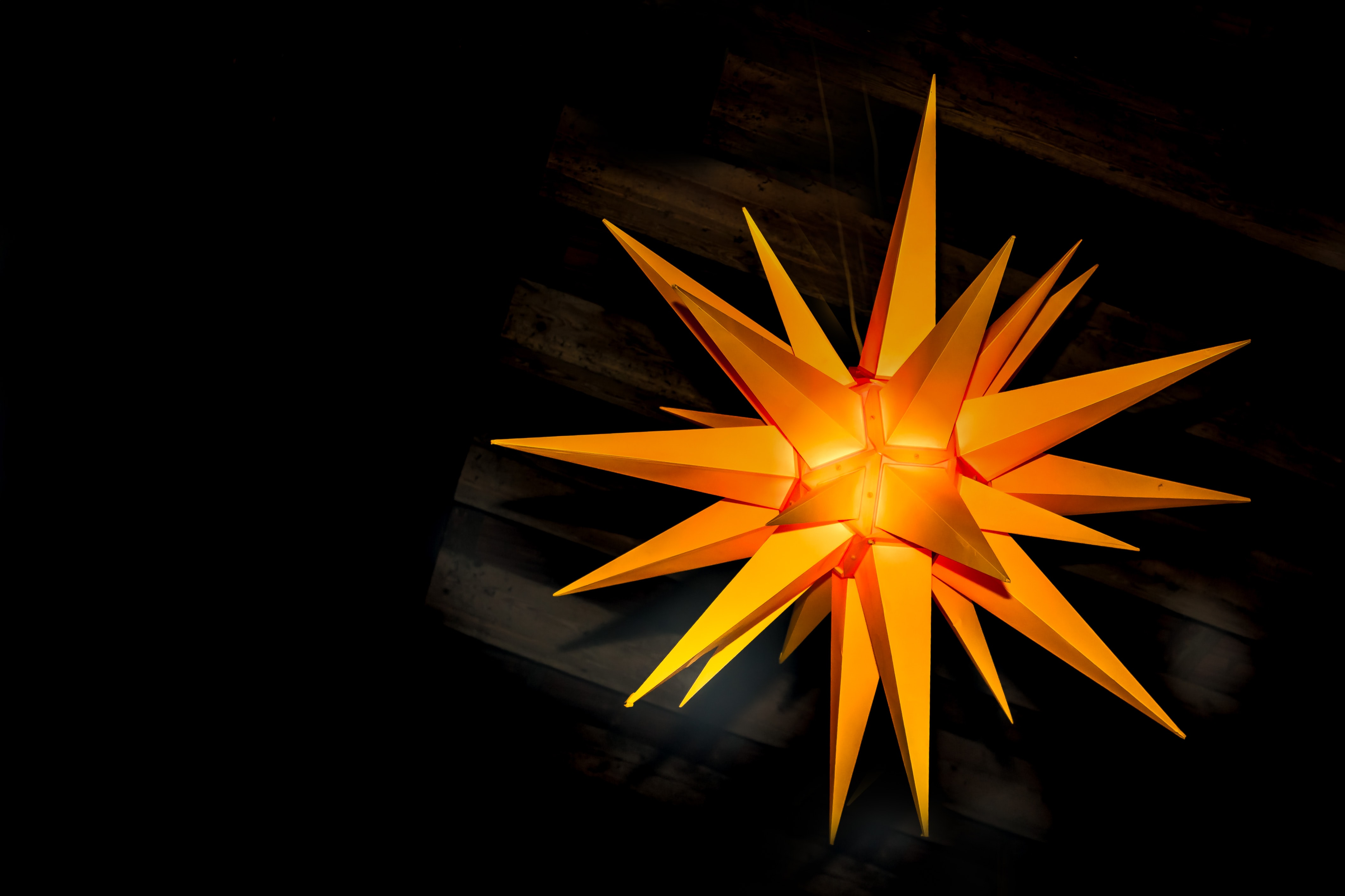 An orange decoration in the shape of multi-pointed star hanging from a ceiling