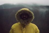 person wearing yellow parka jacket near mountain