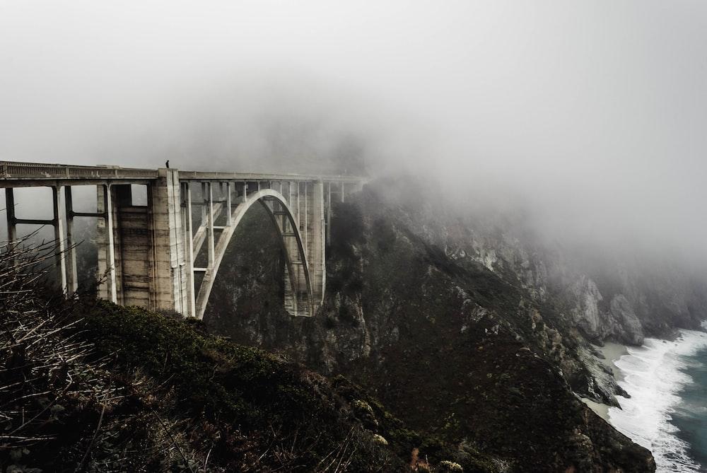 white concrete bridge covered with fogs