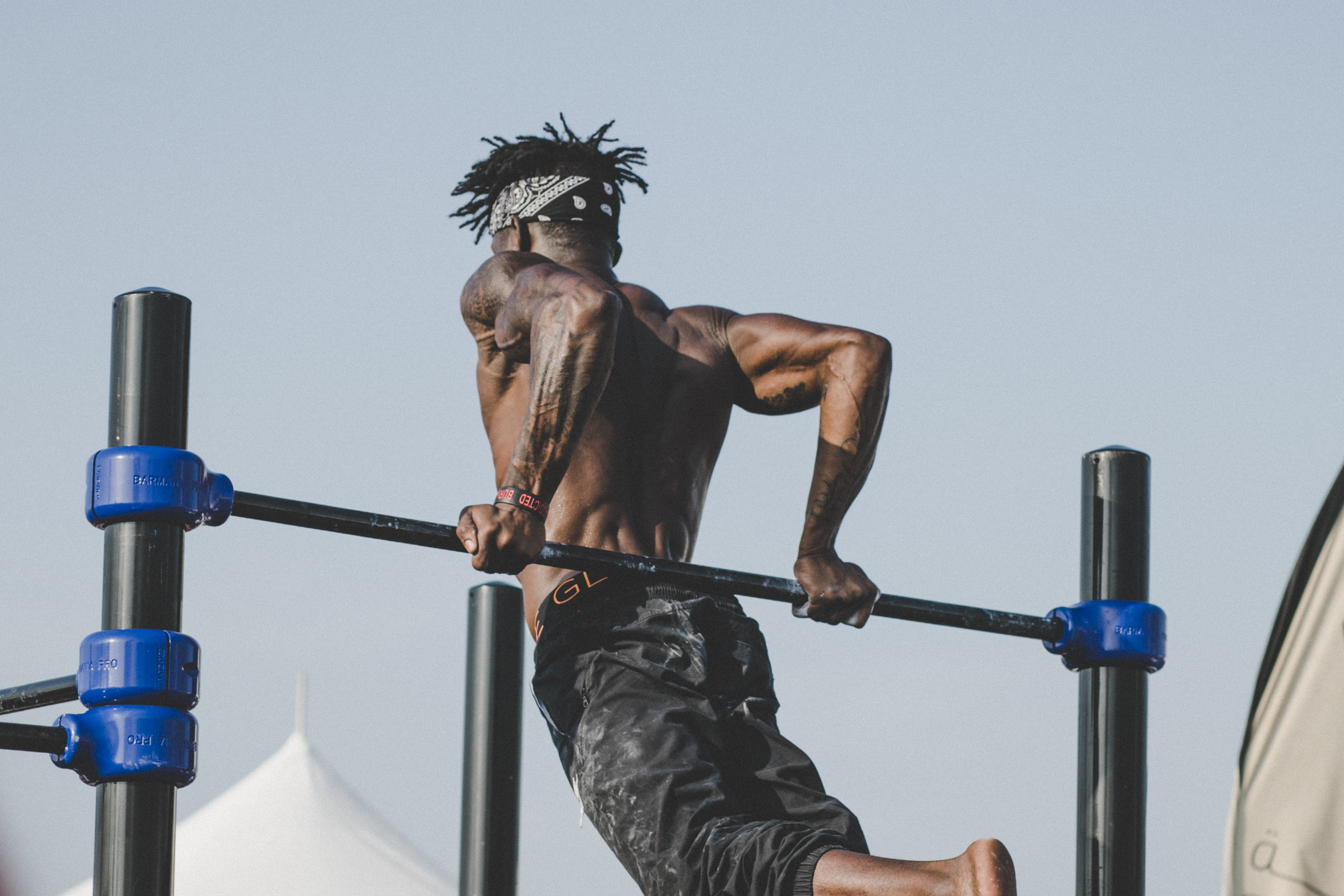 A shirtless man exercising and doing a tricep dip in Dubai