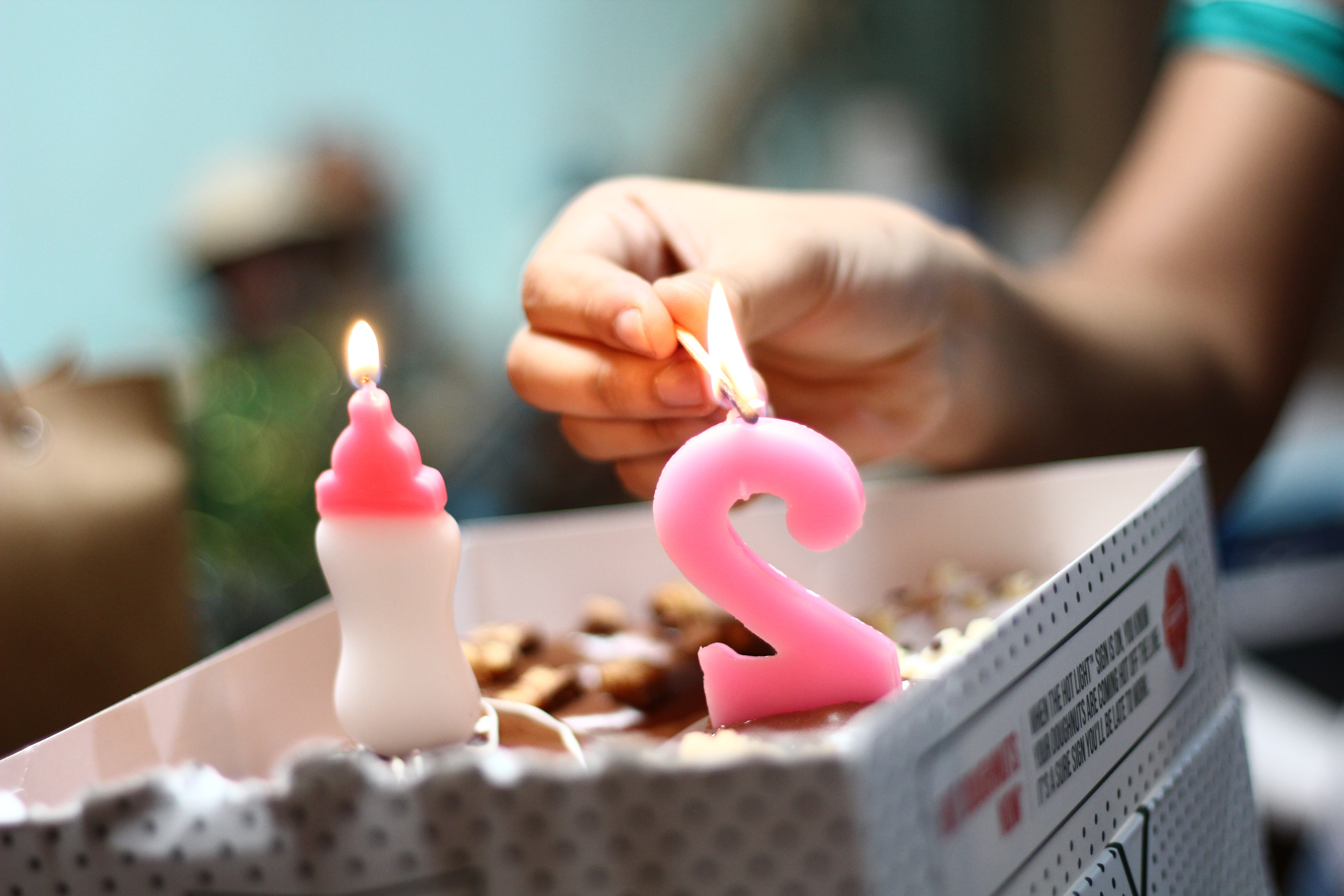 person lighting number 2 candle