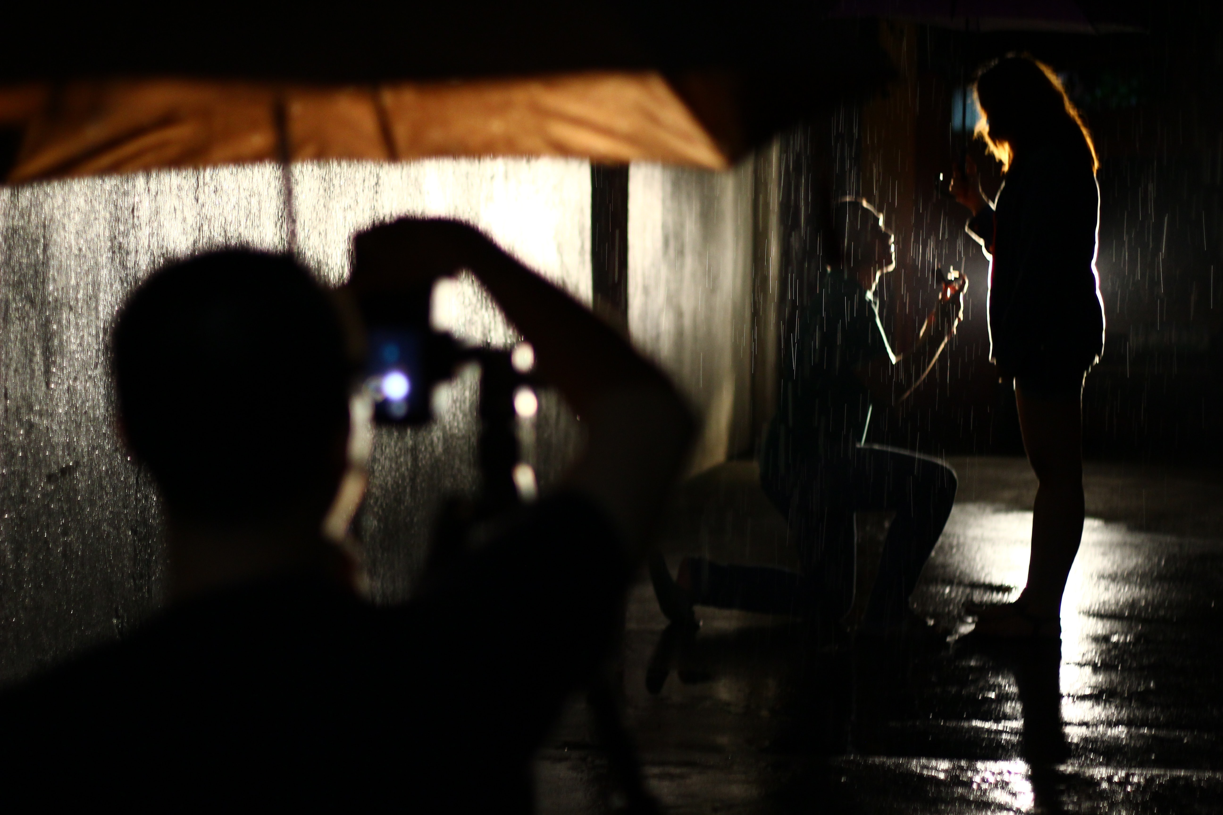 A man proposes to the woman in the nighttime rain. Someone with an umbrella photographs them.