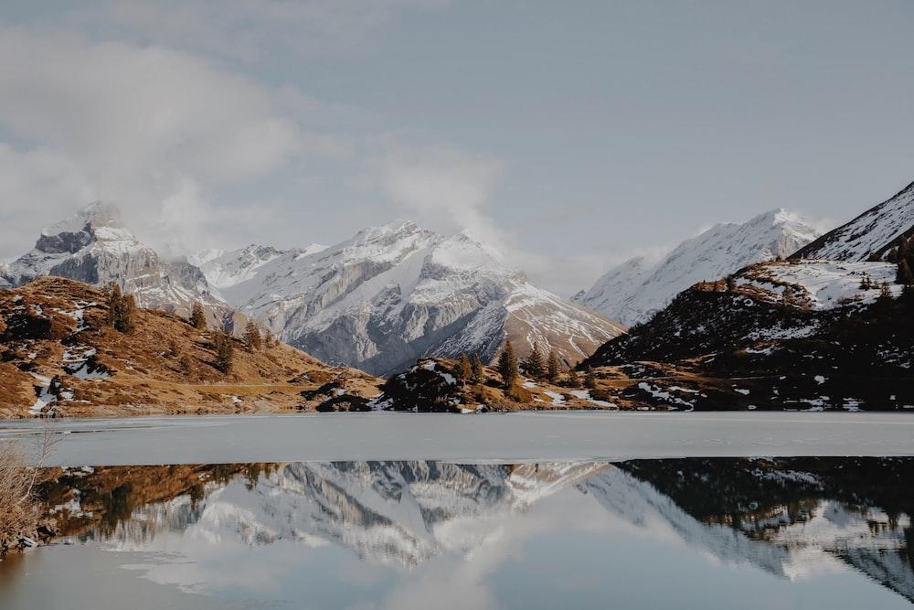 The half-frozen surface of a lake near snowy mountain peaks in Trübsee