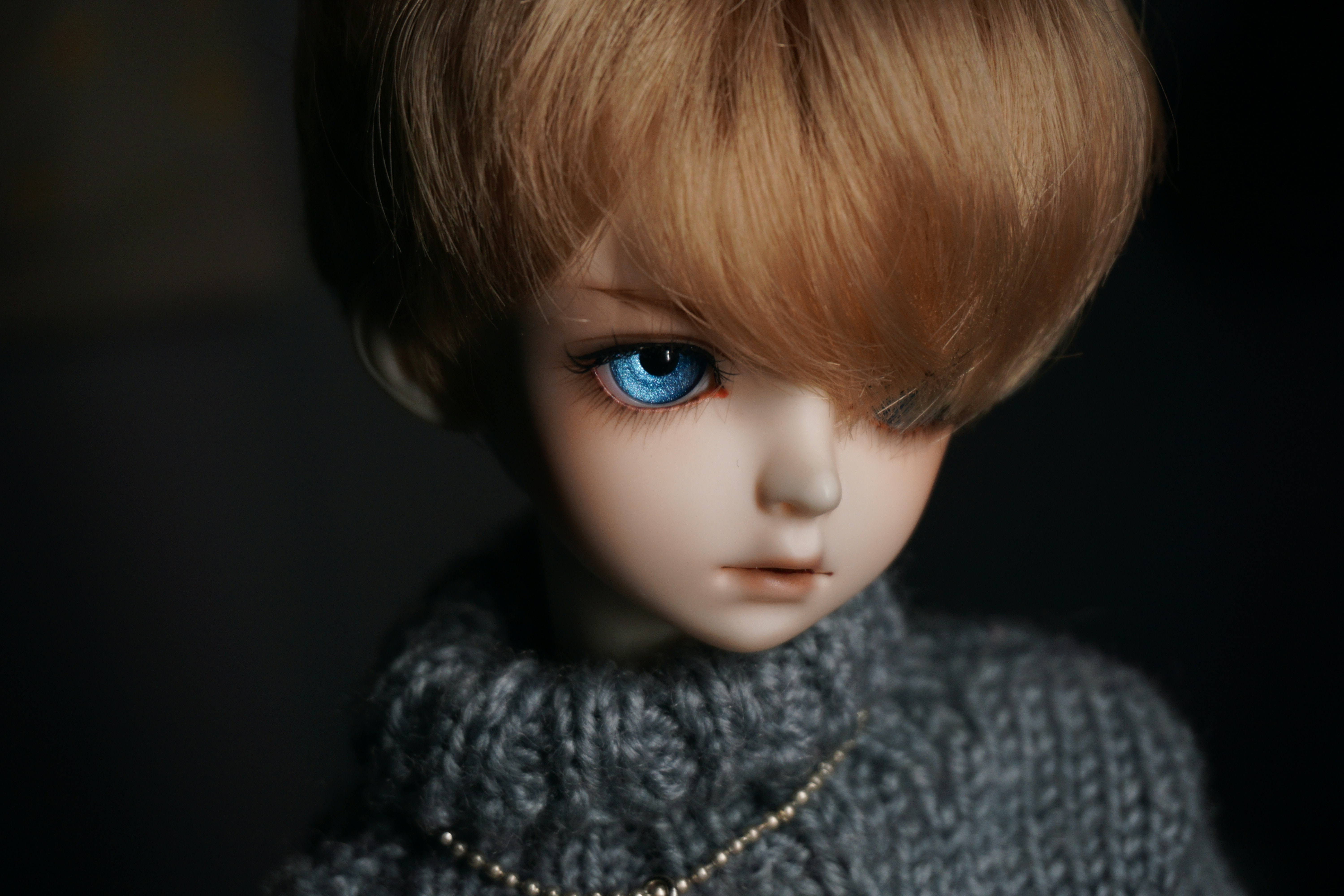 Creepy realistic doll with blue eyes and swoopy hair