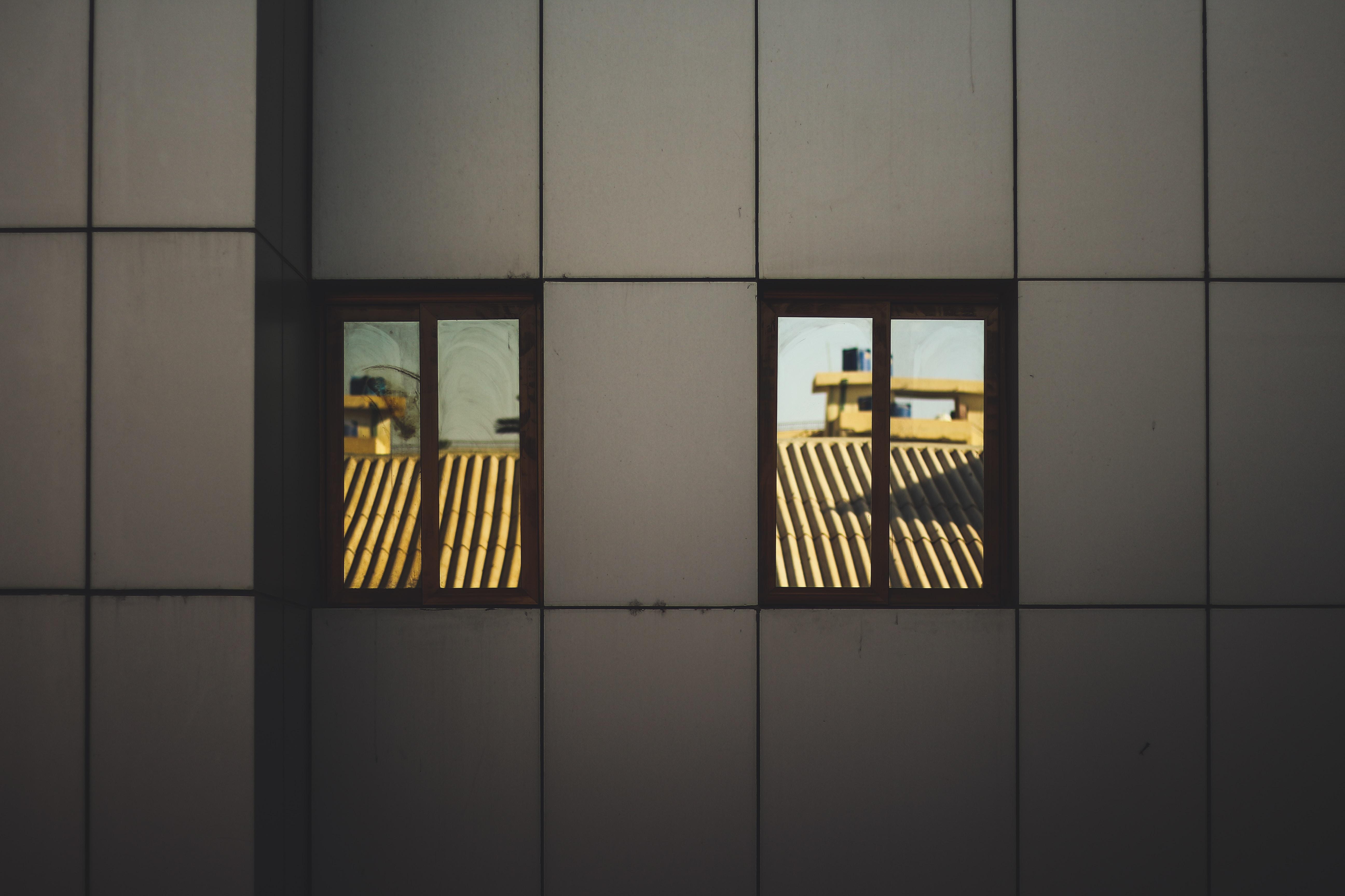 Two small windows in a tiled facade