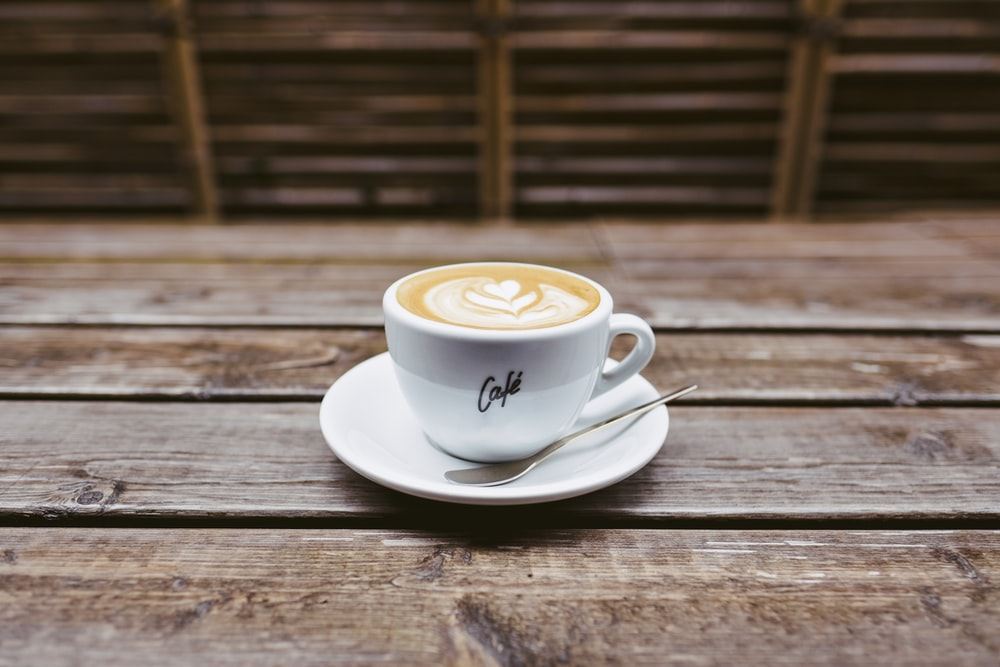 coffee latte on white ceramic saucer beside spoon