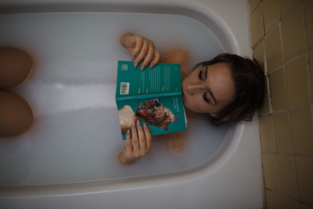 woman lying on bathtub with green book