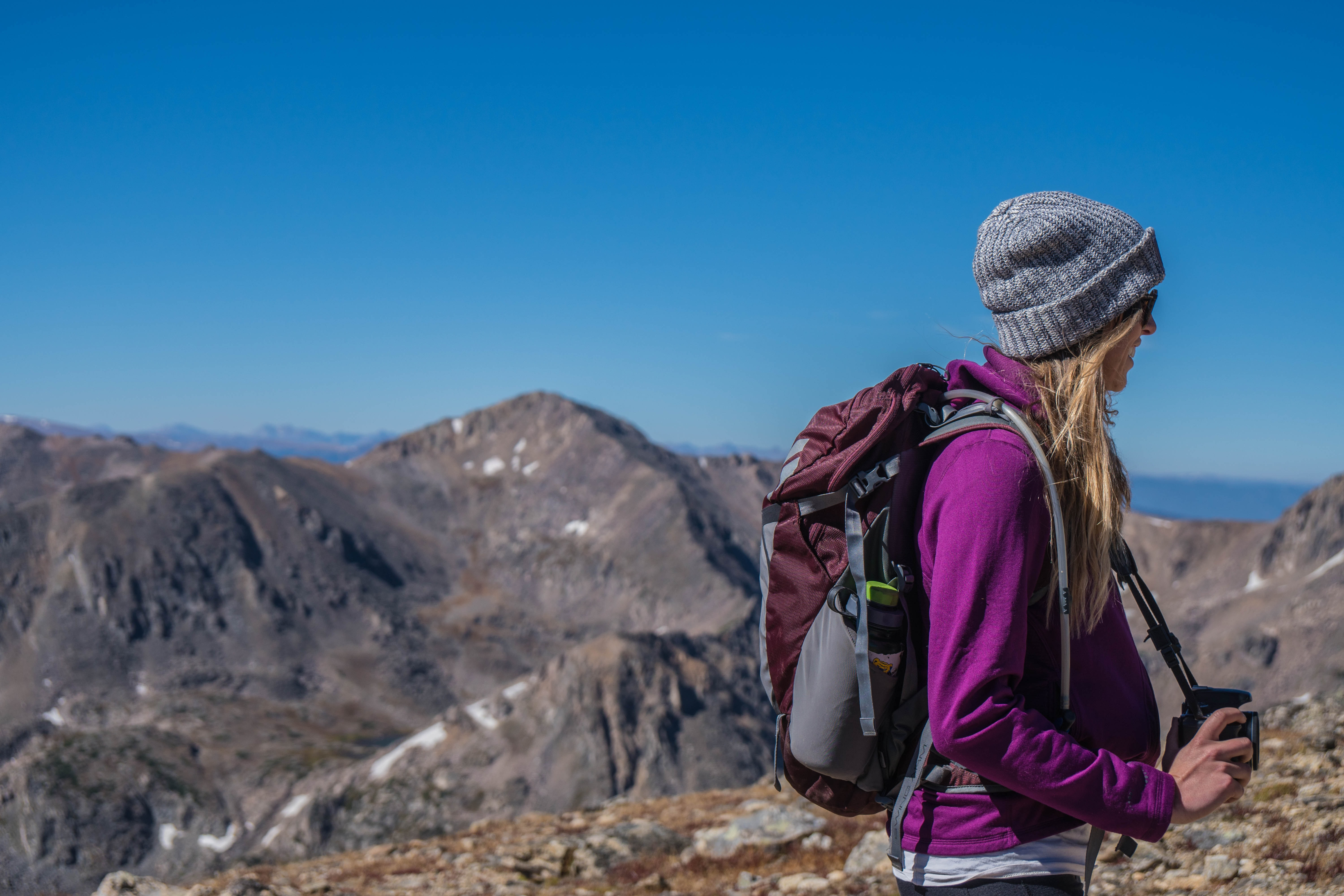 A woman in a backpack and knit cap holds a camera while hiking at James Peak