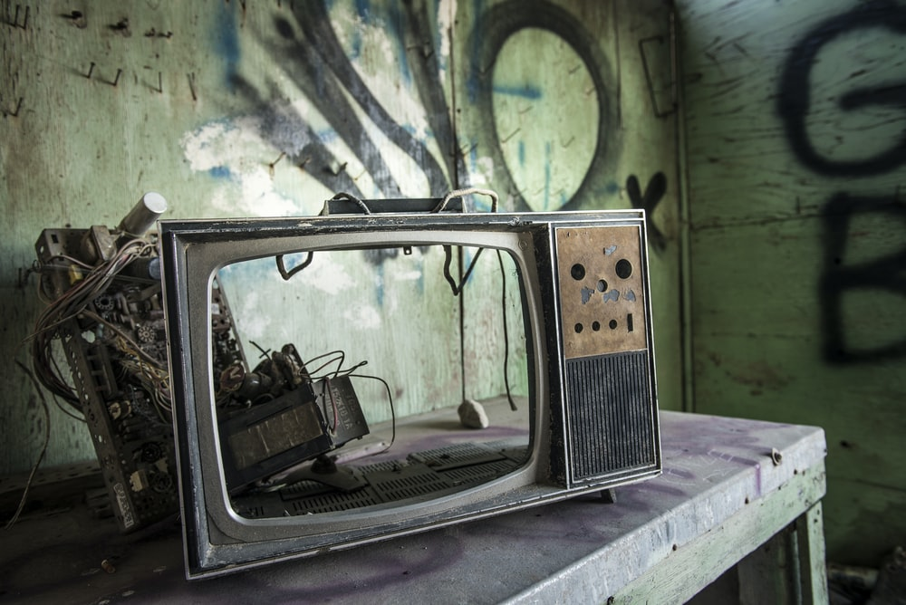 vintage TV on gray wooden table inside room