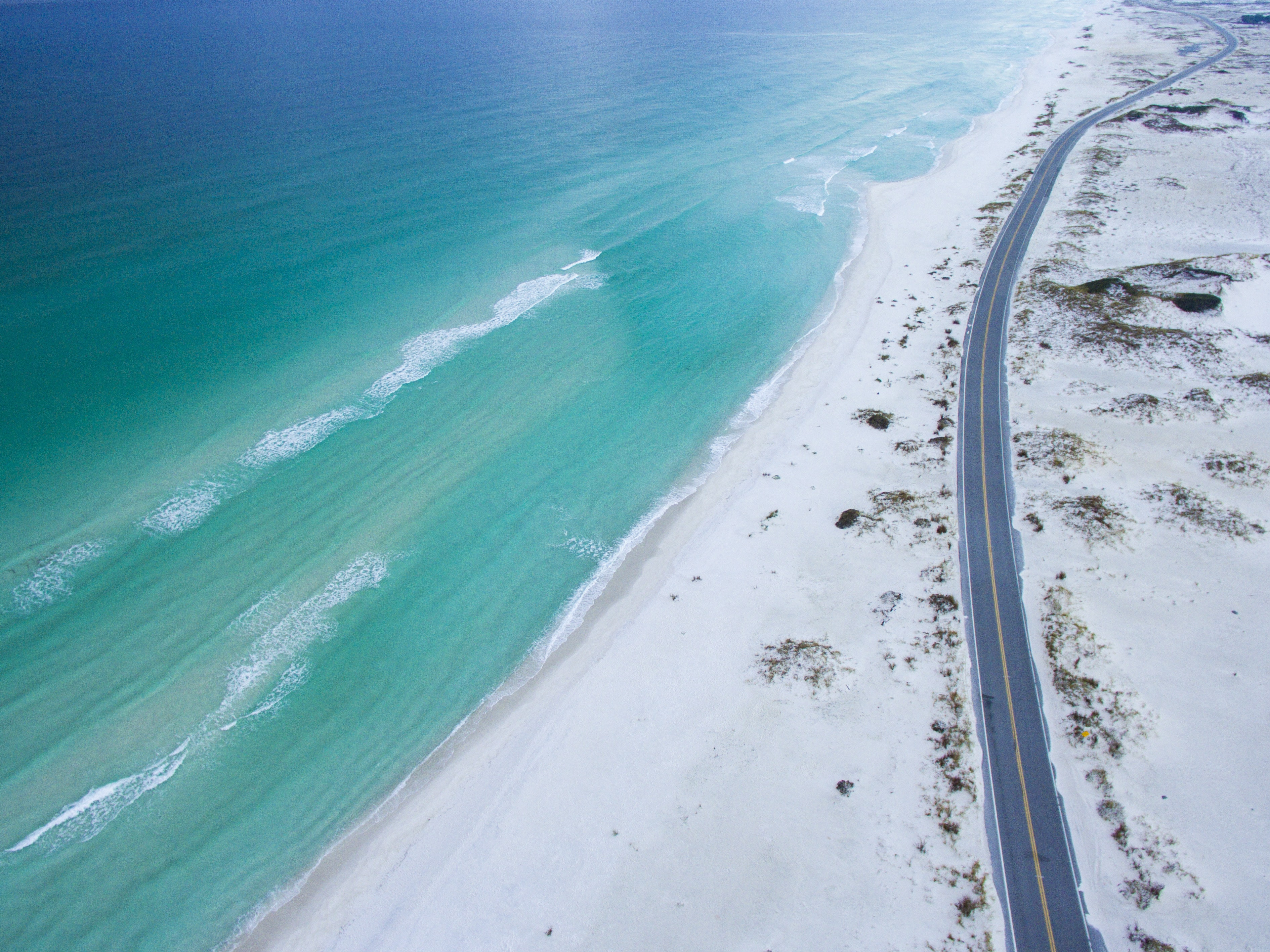 Drone view of a road along the sand beach coastline at Gulf Breeze, Florida, United States