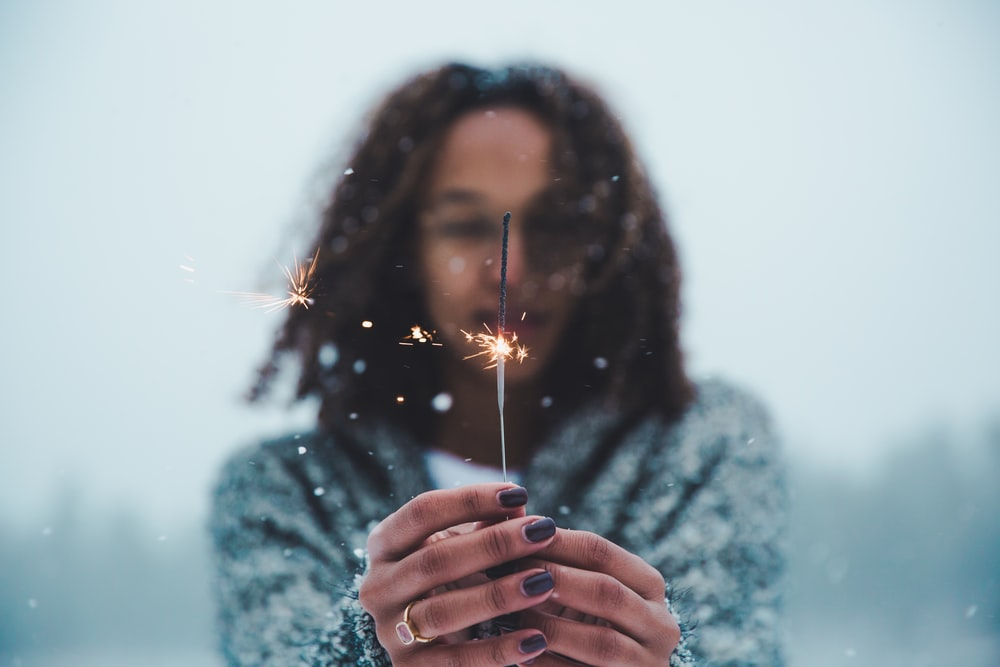 selective focus photography of person holding lighted sparkler