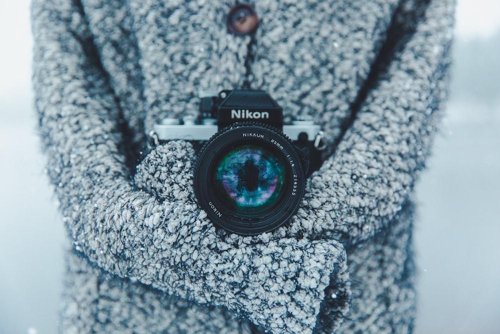 person holding black and gray Nikon DSLR camera