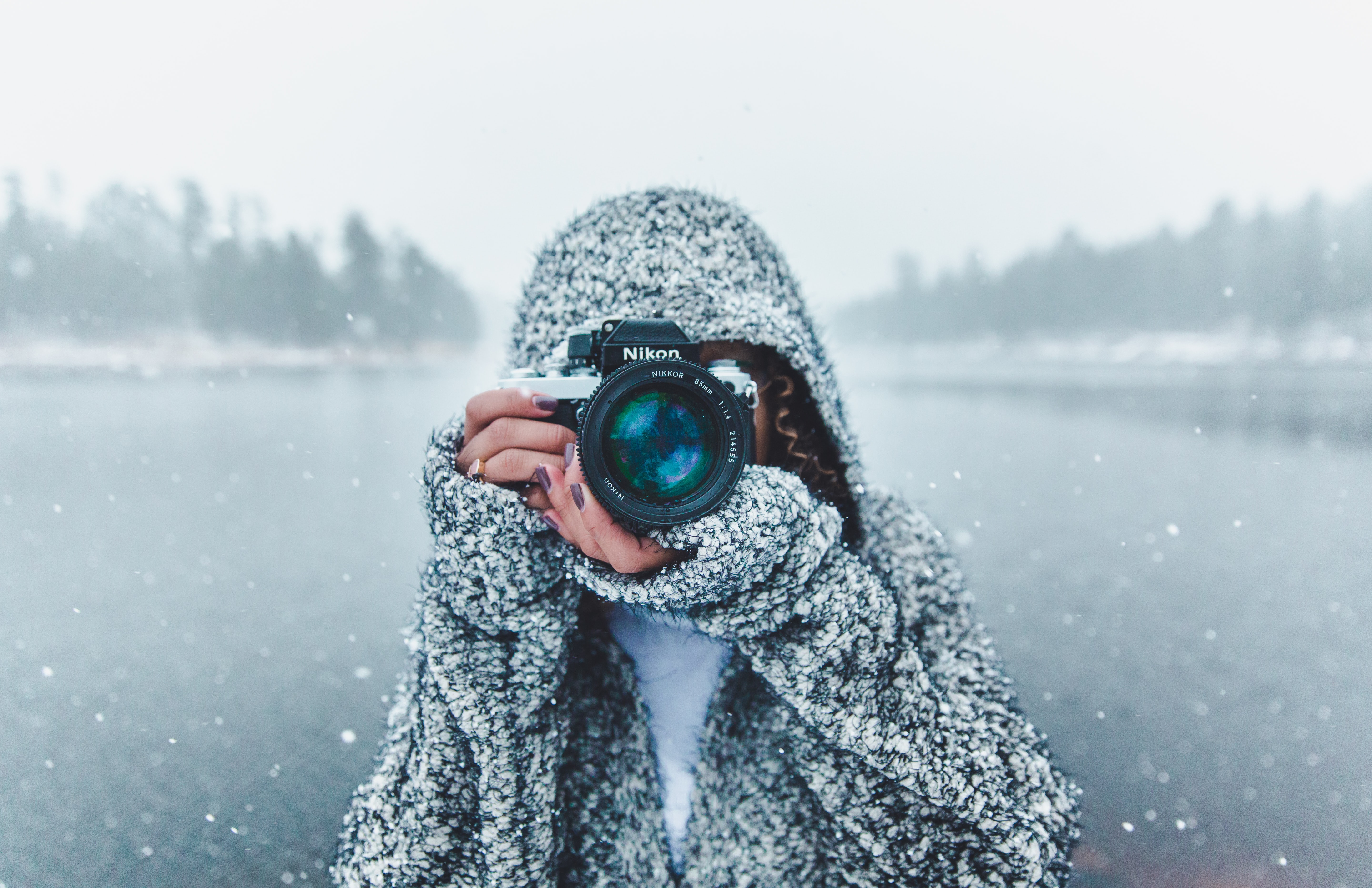 A woman taking a photo while standing over a lake with snow falling around her