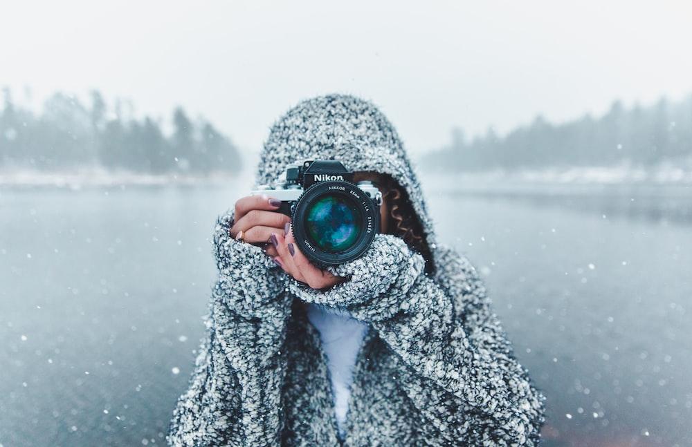 woman using Nikon DSLR camera
