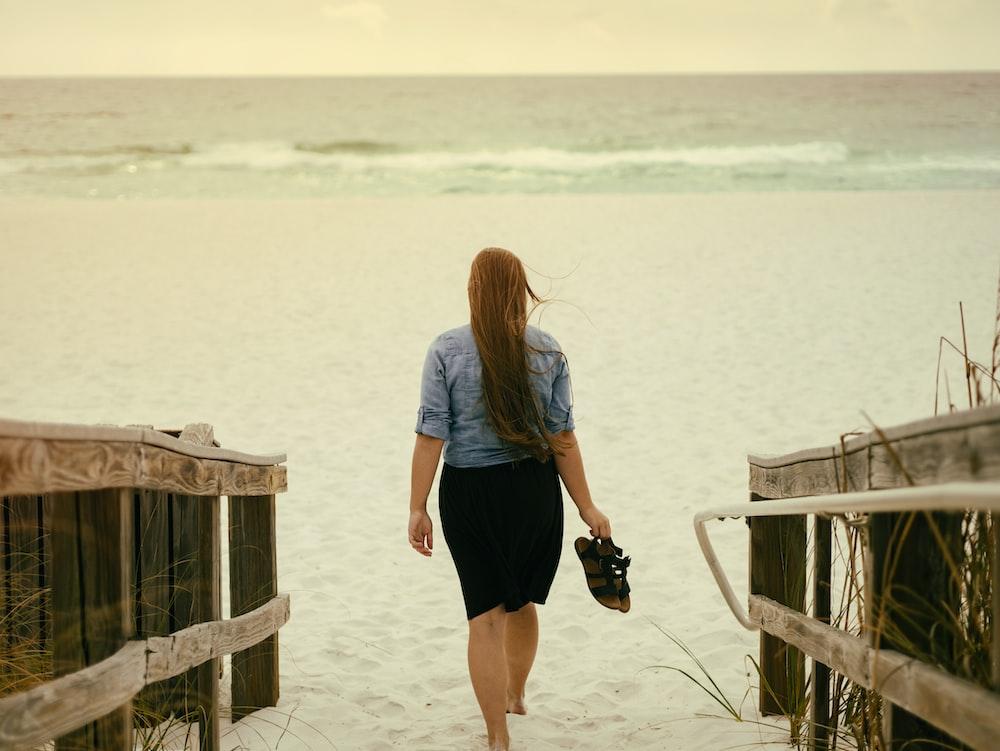 woman holding sandal walking on sand