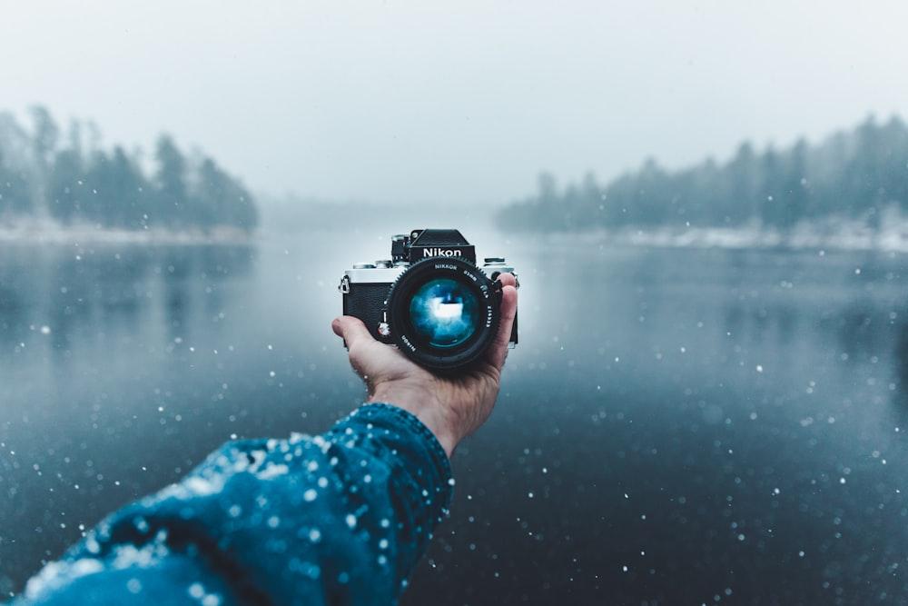 person taking selfie using Nikon DSLR camera