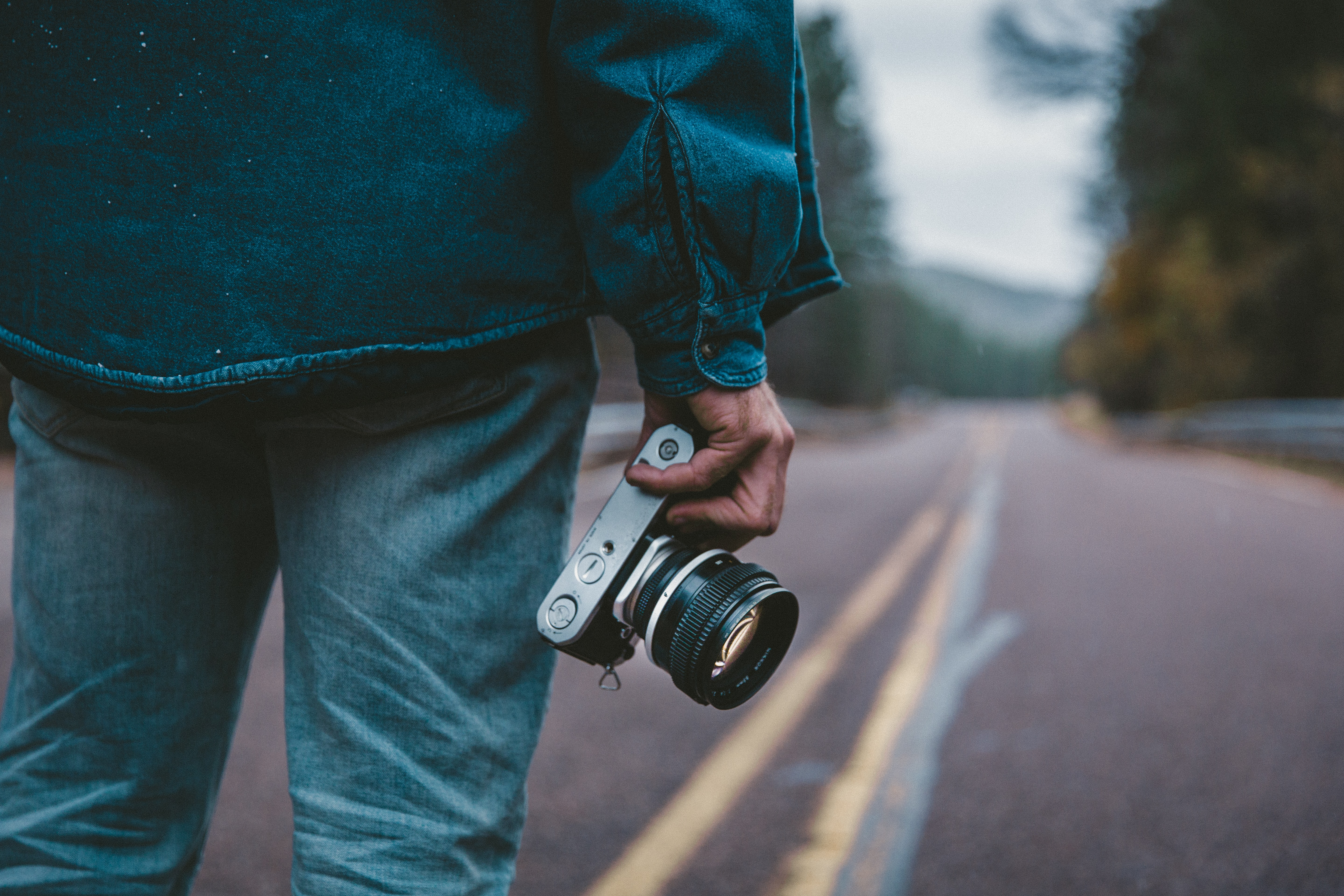 A man in denim clothing stands on an empty paved road holding a camera.