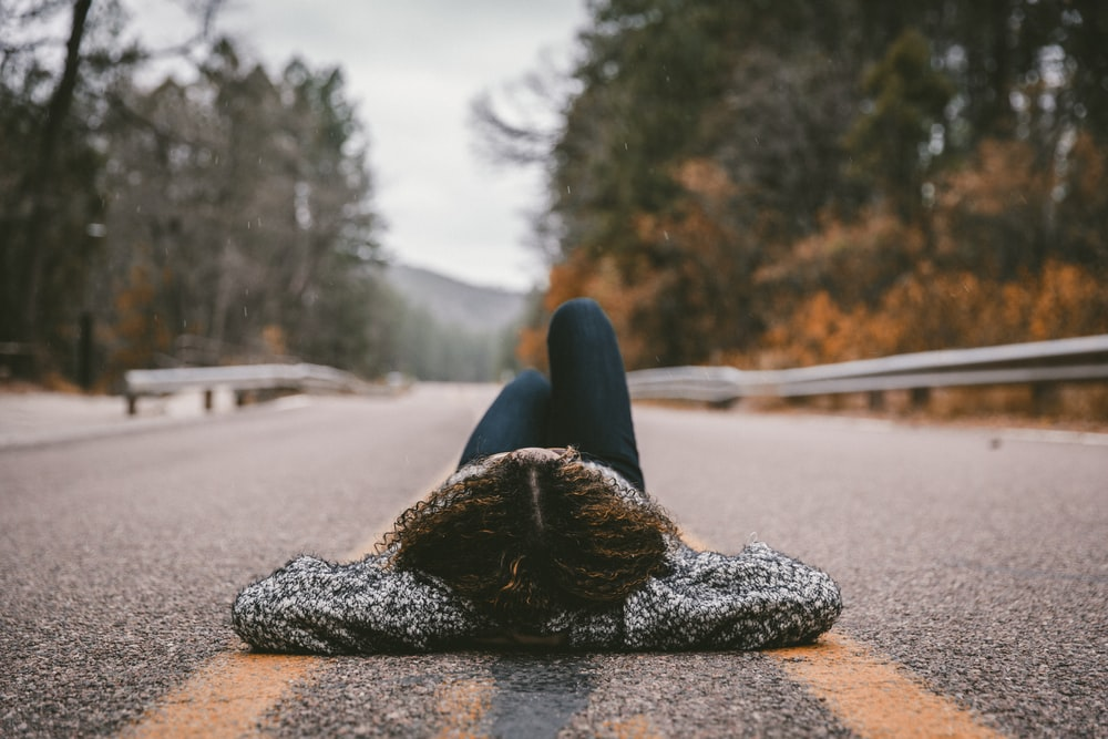 person lying on gray concrete road