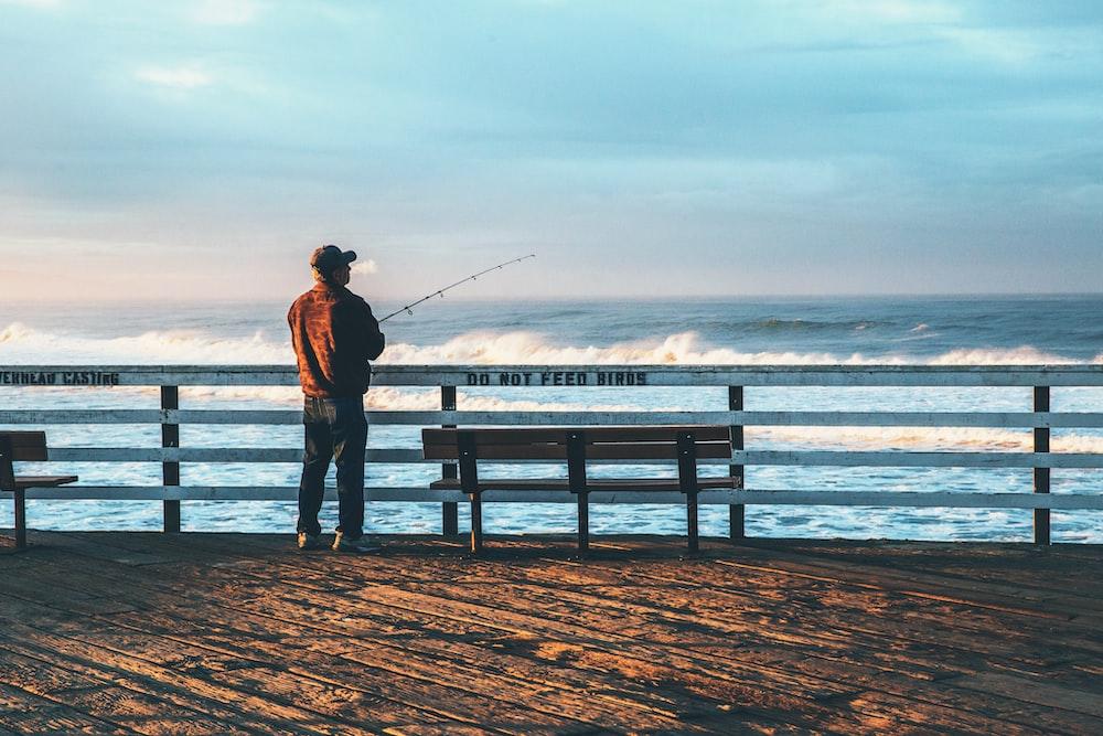 man fishing on seaside