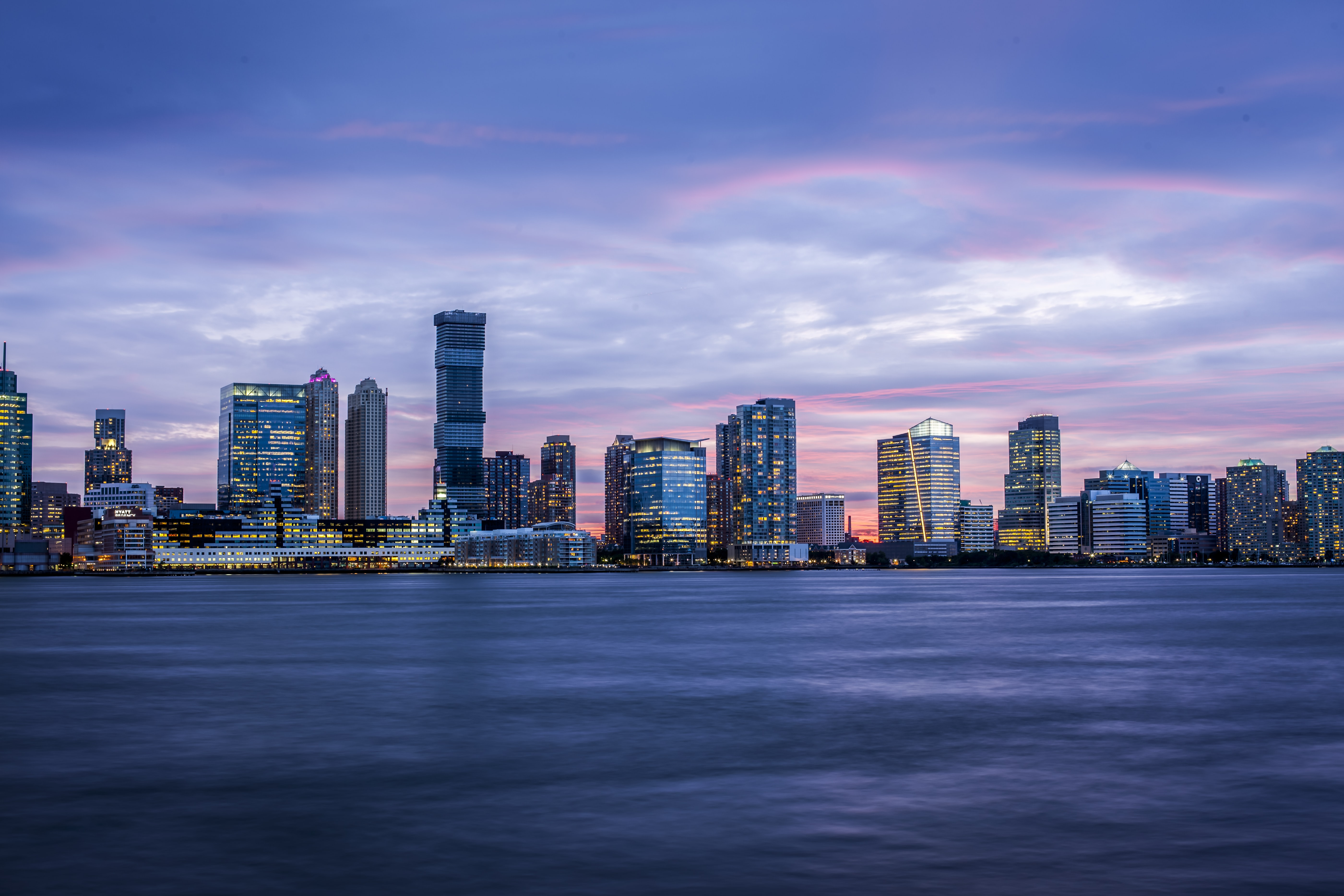 The bright skyline of New York seen from the Hudson River at night