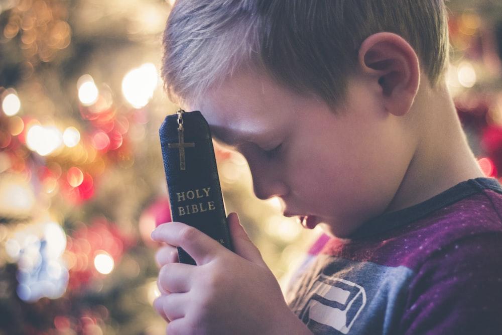boy holding Holy Bible